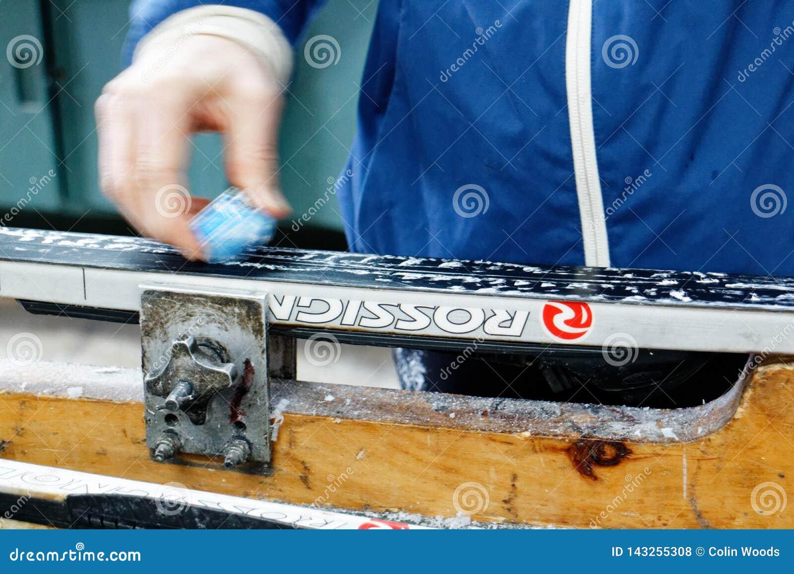 Uma mulher que encera esquis do corta-mato antes do esqui de saída
