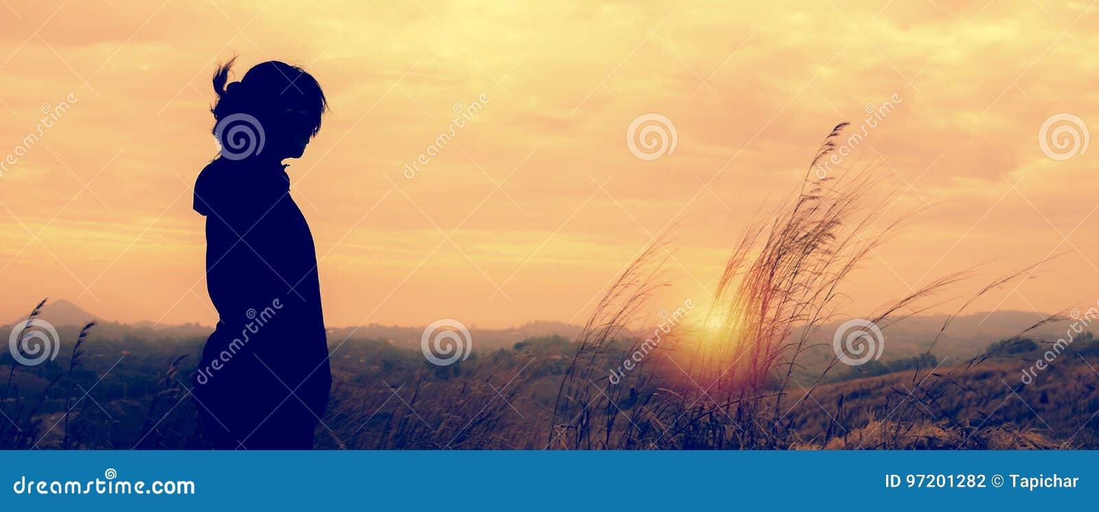 Uma mulher que está apenas na cena do por do sol