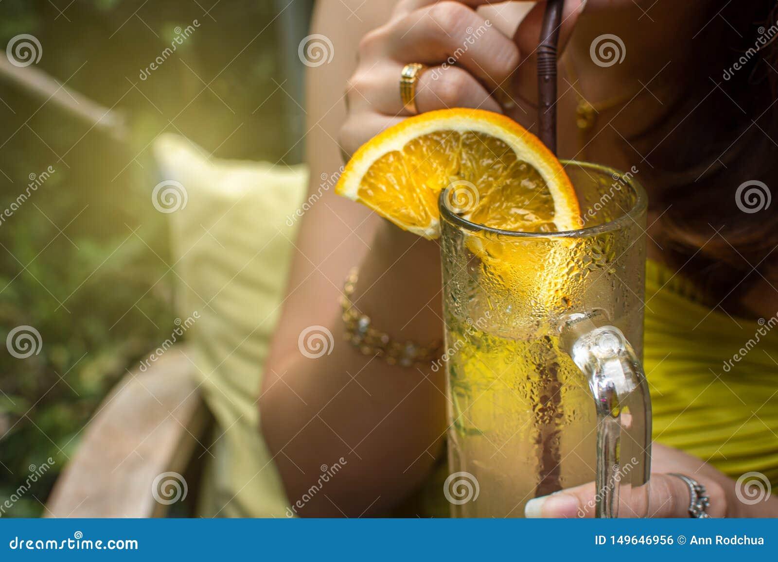 Uma mulher que guarda um vidro da limonada para a bebida