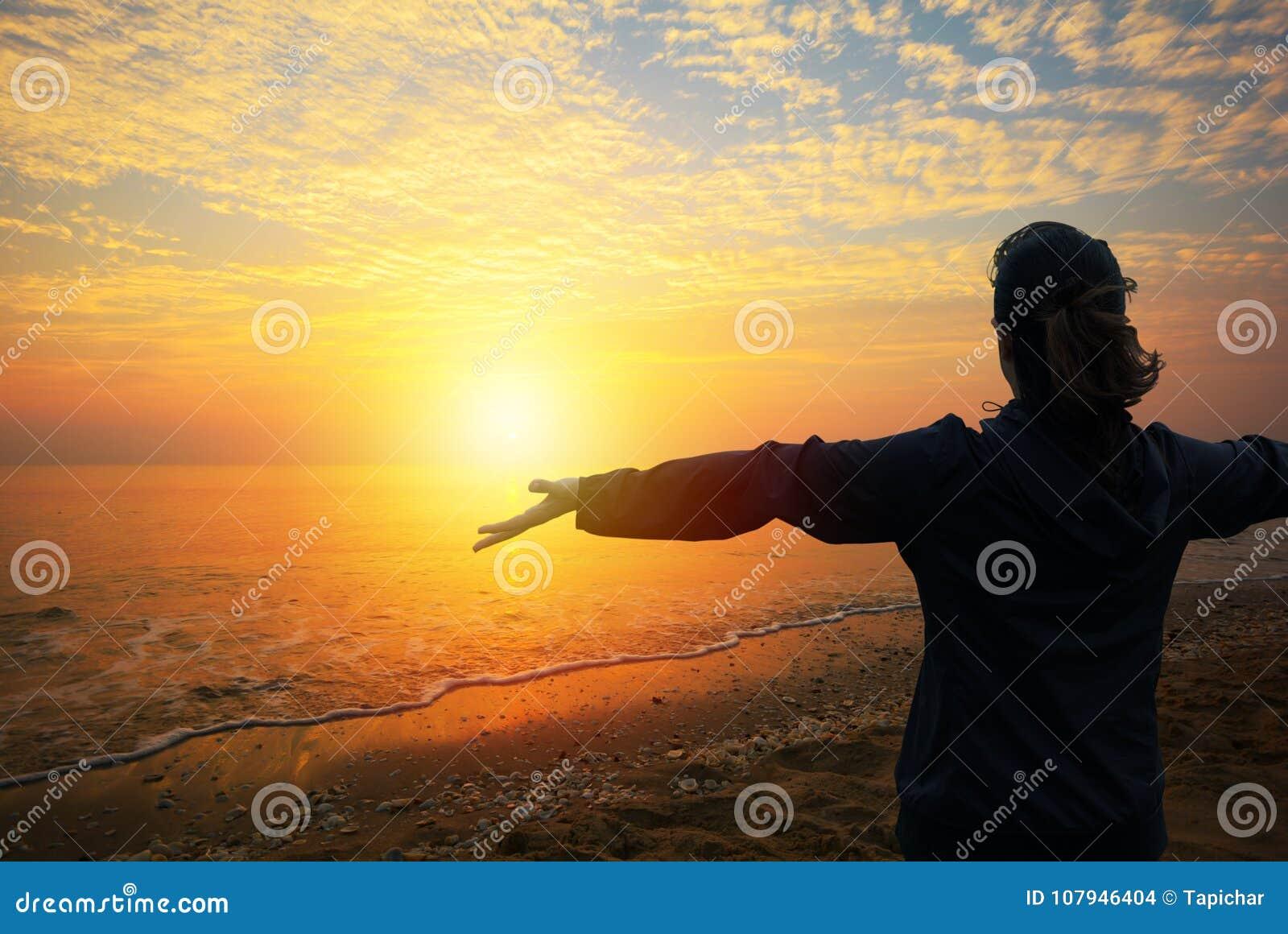 Uma mulher que olha ao por do sol na praia