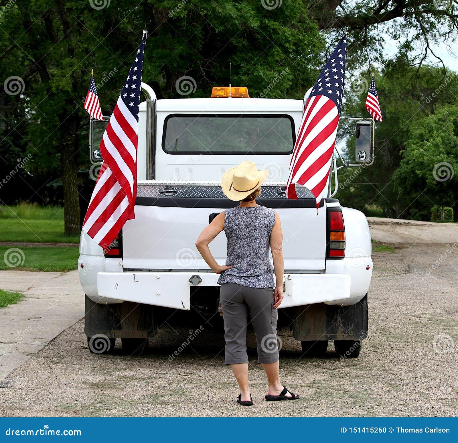 Uma mulher que olha as bandeiras americanas indicadas em um camionete