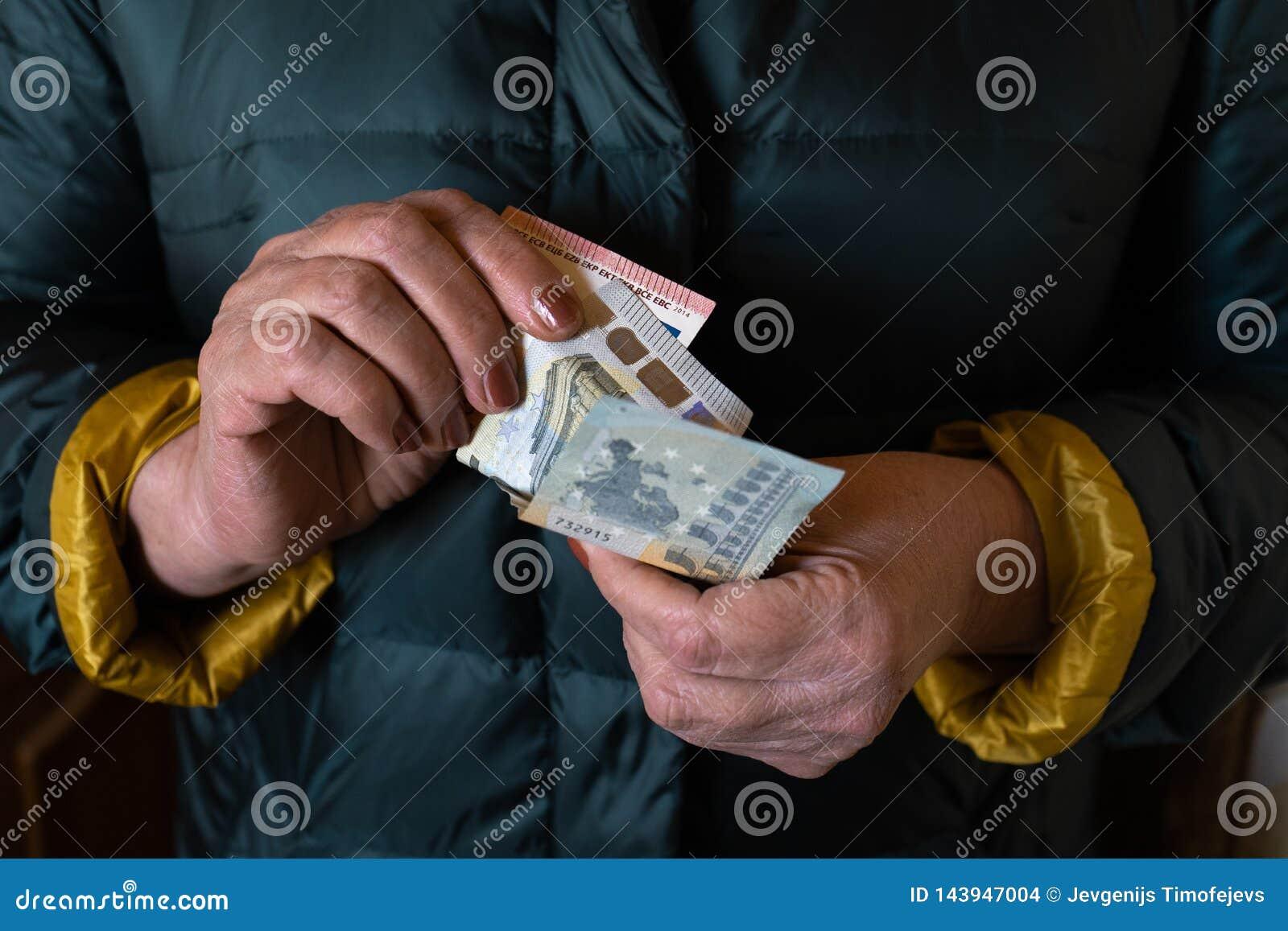 Uma mulher superior mais idosa guarda c?dulas do EURO - pens?o da Europa Oriental do sal?rio