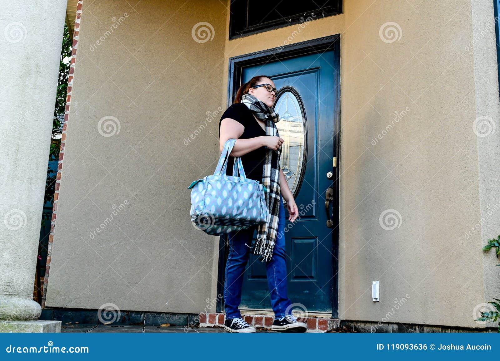 Uma mulher trava sua porta da rua enquanto sae em casa com um saco de duffel sobre um braço