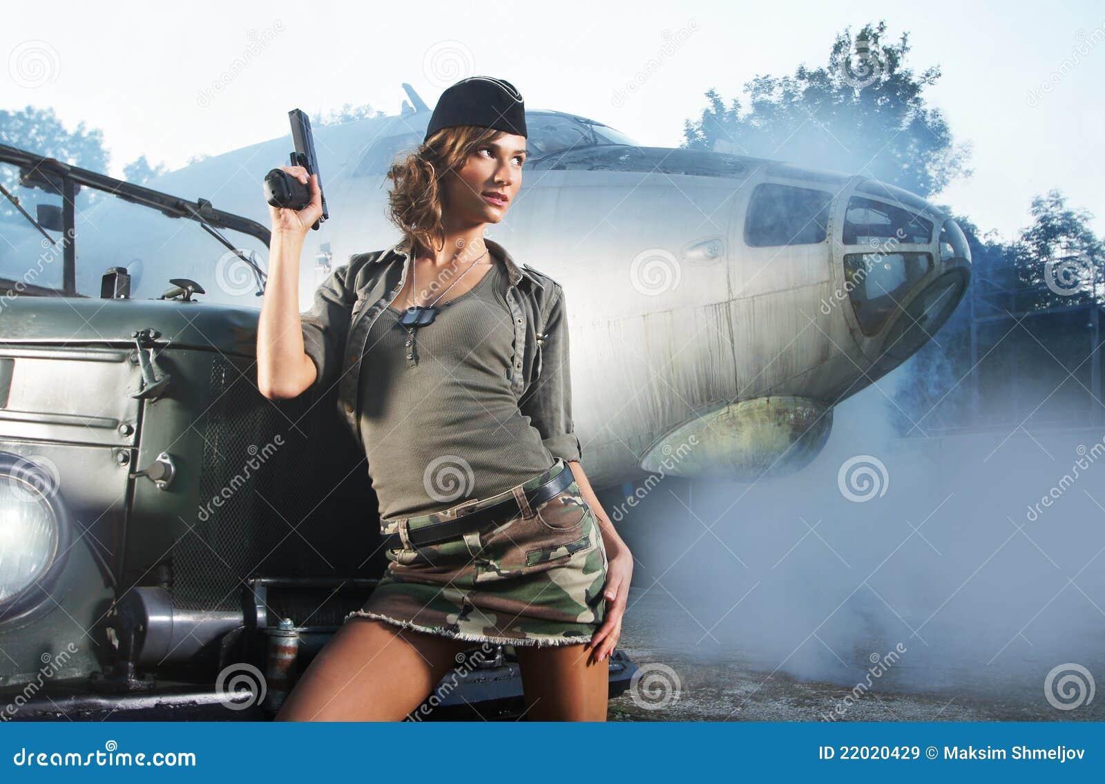 Uma mulher triguenha nova que levanta na roupa militar