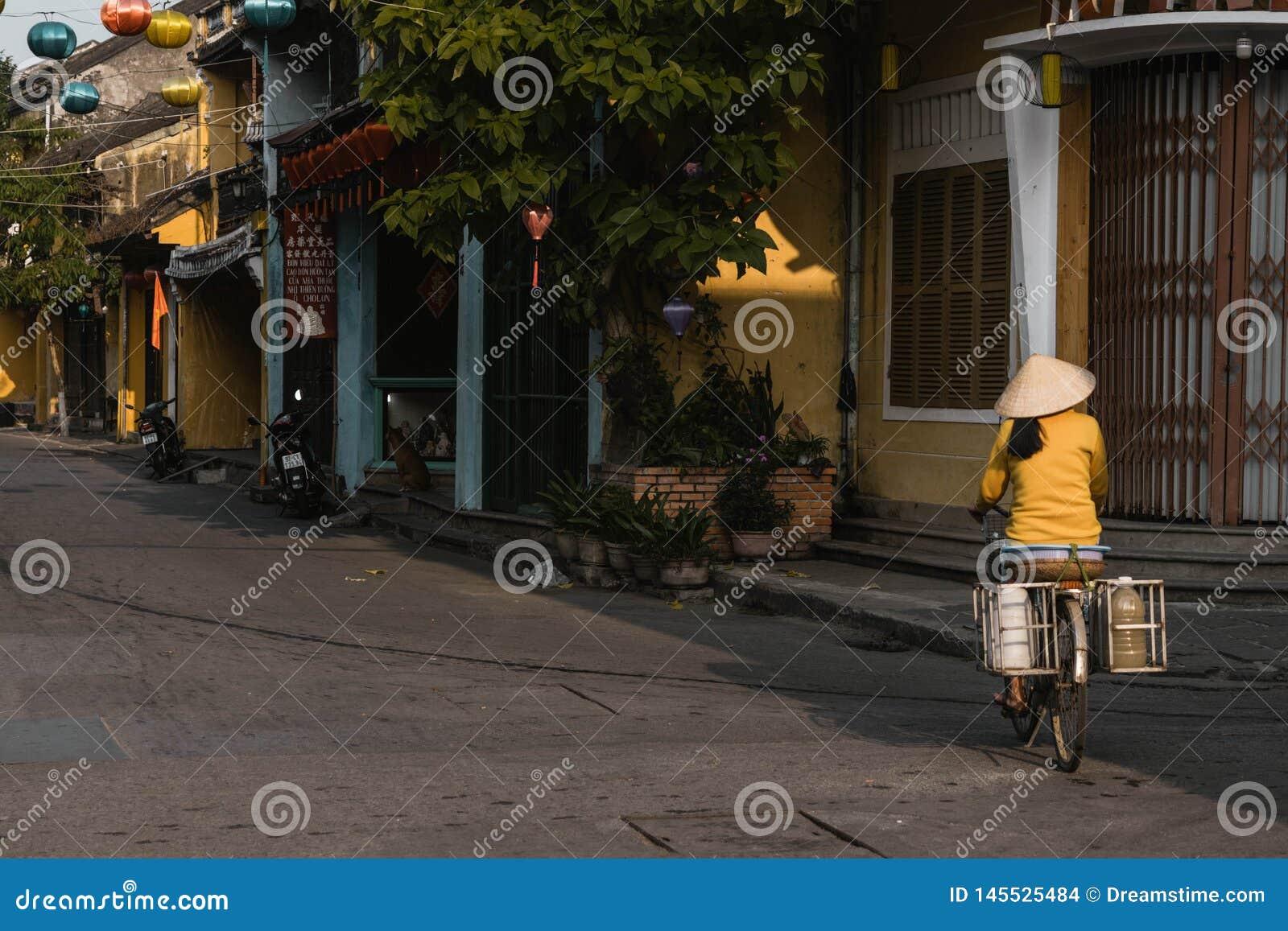 Uma mulher vietnamiana local monta sua bicicleta para trabalhar no hoi