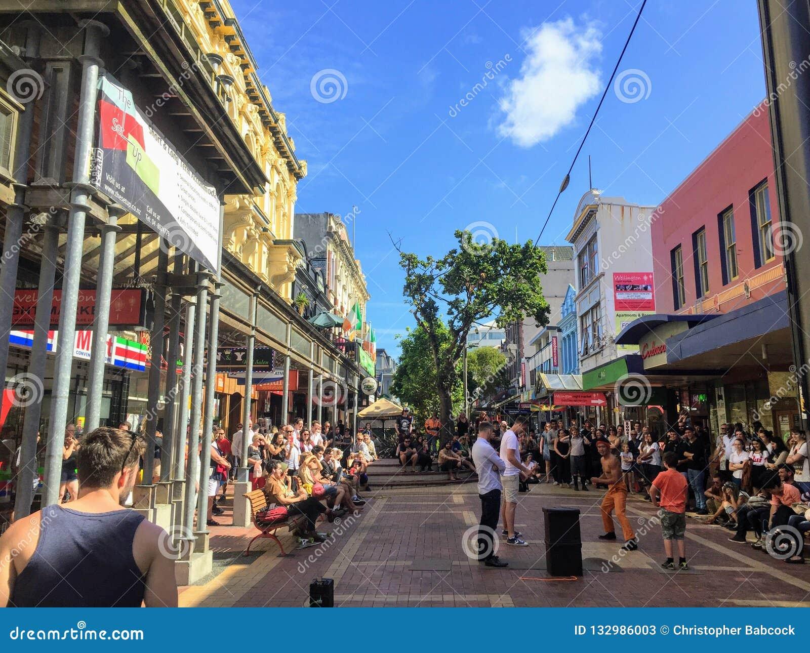Uma multidão embalada de turistas e os locals apreciam um executor local da rua na rua de Cuba em Wellington do centro