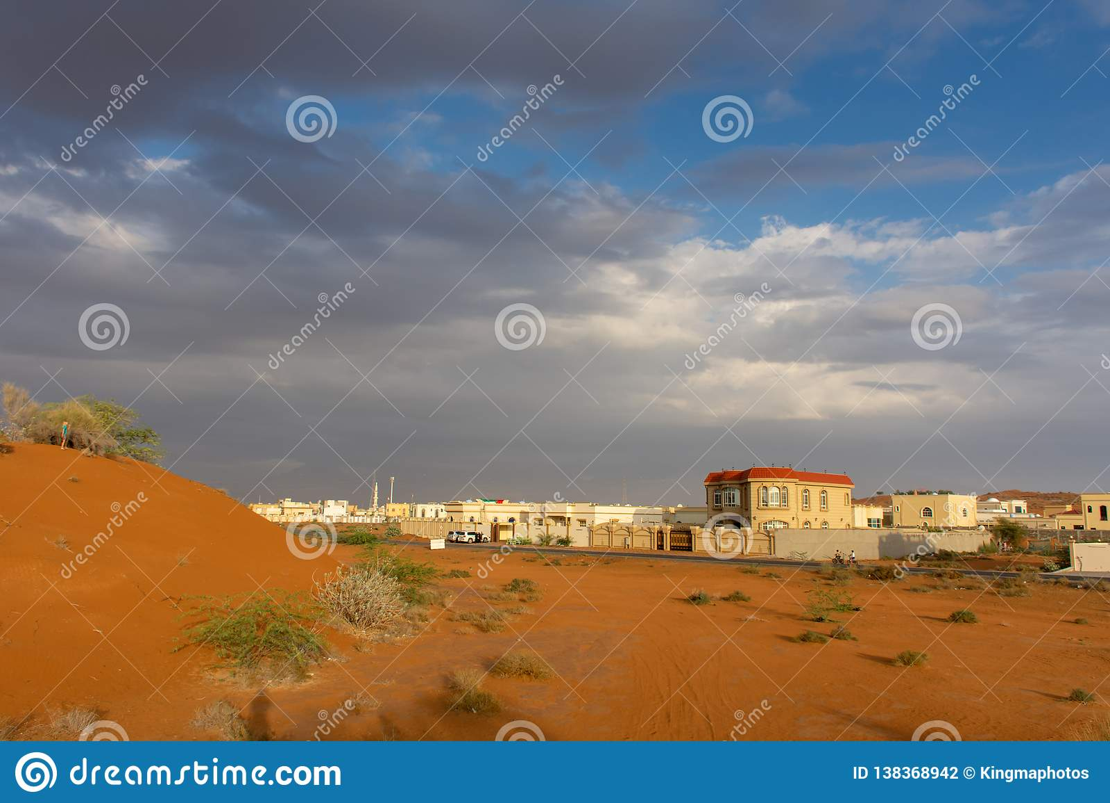 Uma noite tormentoso nos UAE com nuvens escuras e o céu azul sobre a cidade e as dunas de areia alaranjadas