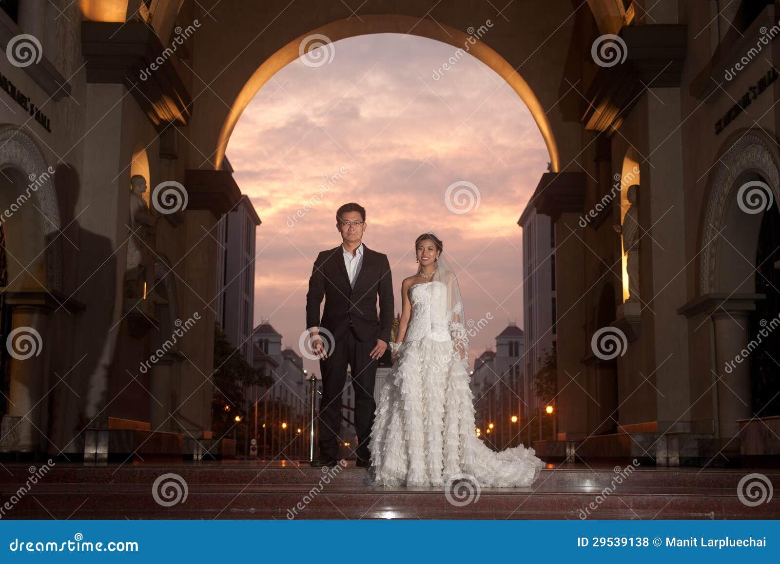 Uma noiva bonita e um noivo considerável na igreja cristã durante o casamento.