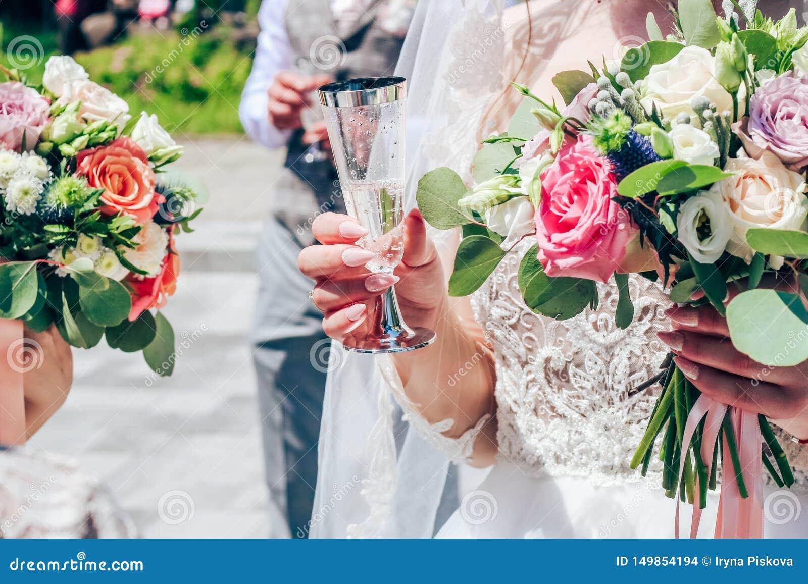 Uma noiva com os pregos nude longos está guardando um vidro do champanhe Close-up