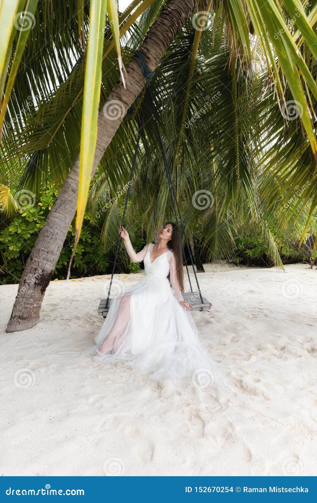 Uma noiva em um vestido branco está montando em um balanço sob uma palmeira grande