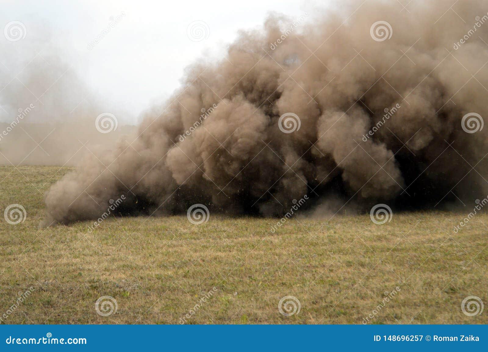 Uma nuvem de poeira forma o furac?o em um campo de explora??o agr?cola