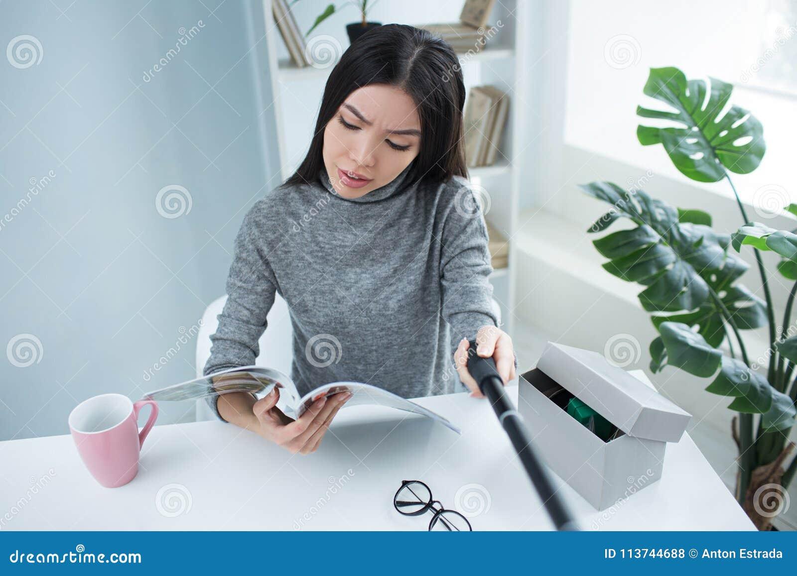 Uma outra imagem do selfie de uma menina que a finja está lendo um jornal A moça está sentando-se em uma sala agradável próximo