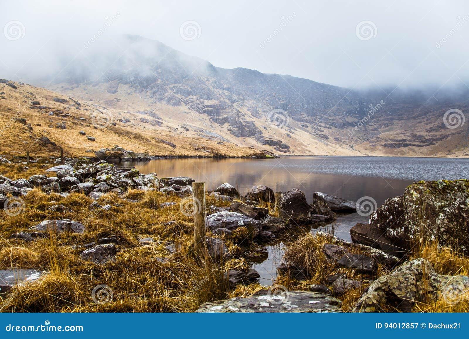 Uma paisagem irlandesa bonita da montanha com um lago na mola