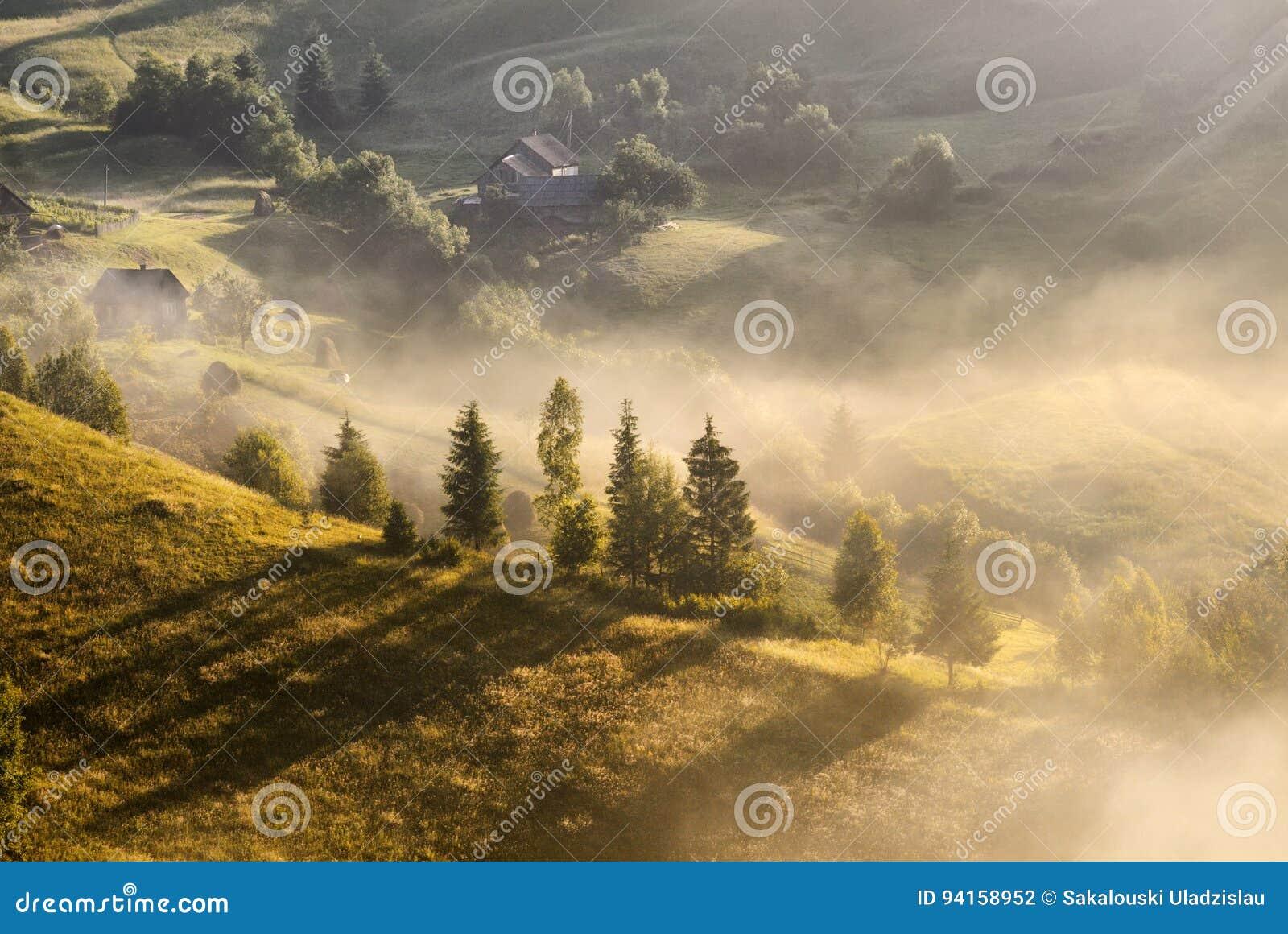 Uma paisagem nevoenta do outono bonito com casas sós e os montes ensolarados Paisagem rural Carpathian no por do sol em cores do