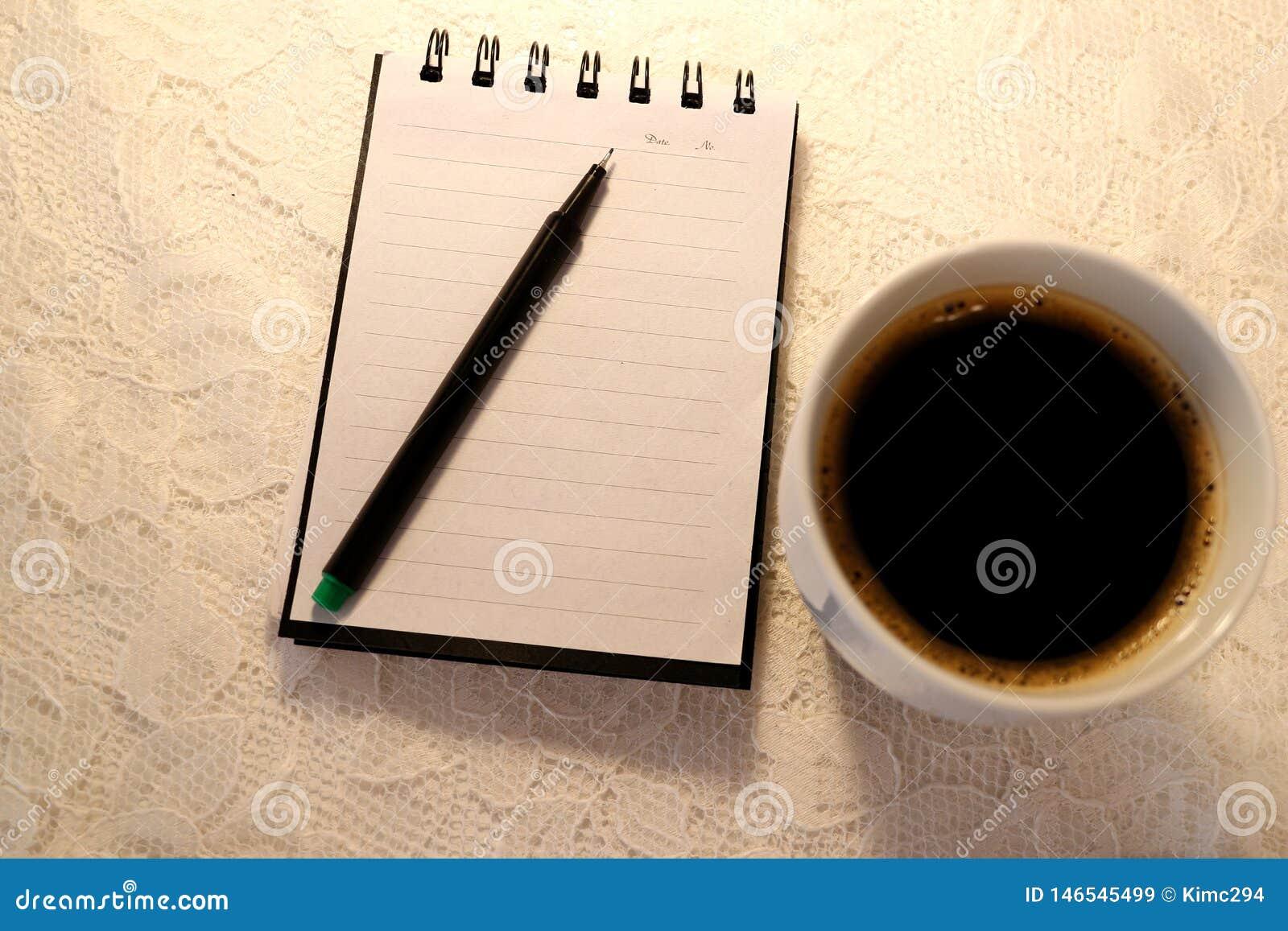 Uma pena sentida verde encontra-se sobre um caderno aberto Um copo de suportes frescos do café preto no lado