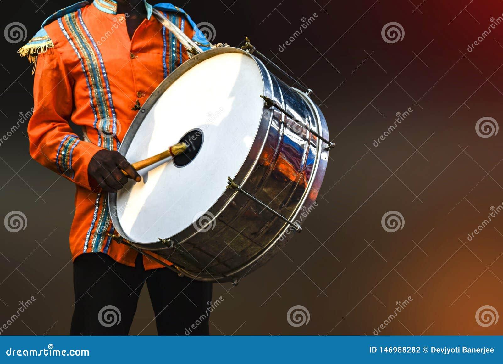 Uma pessoa que joga a pele de tambor, - a pele de tambor é um instrumento musical que seja soado sendo golpeado ou ser raspada po