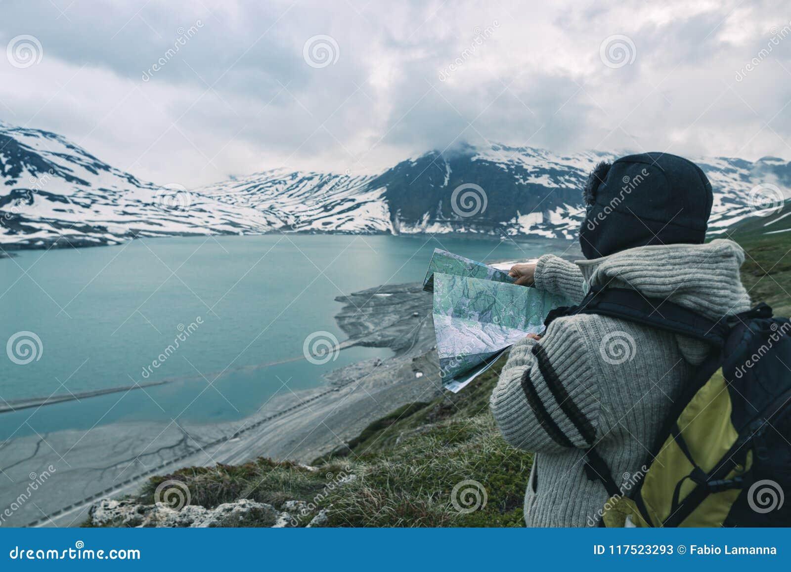 Uma pessoa que olha o mapa trekking, o céu dramático no crepúsculo, o lago e montanhas nevado, sentimento frio nórdico
