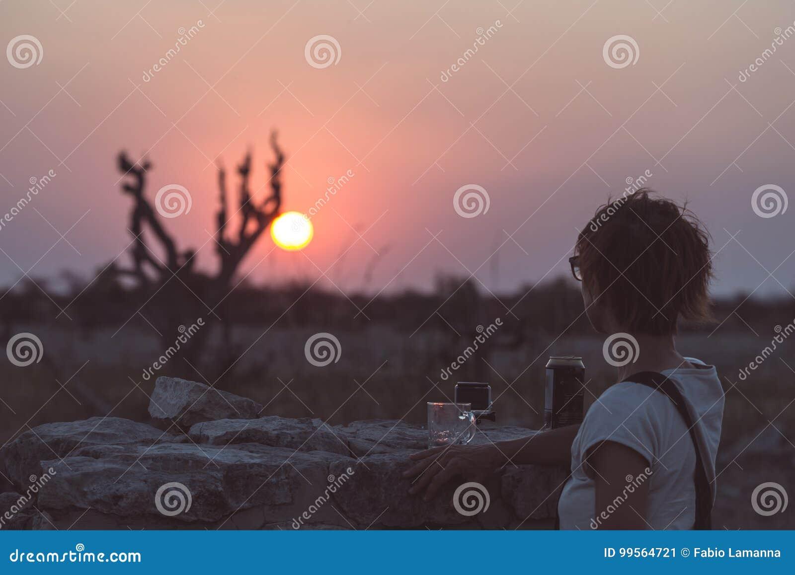 Uma pessoa que tem uma bebida e que olha o por do sol colorido no deserto de Namib, destino do curso em Namíbia, África Conceito