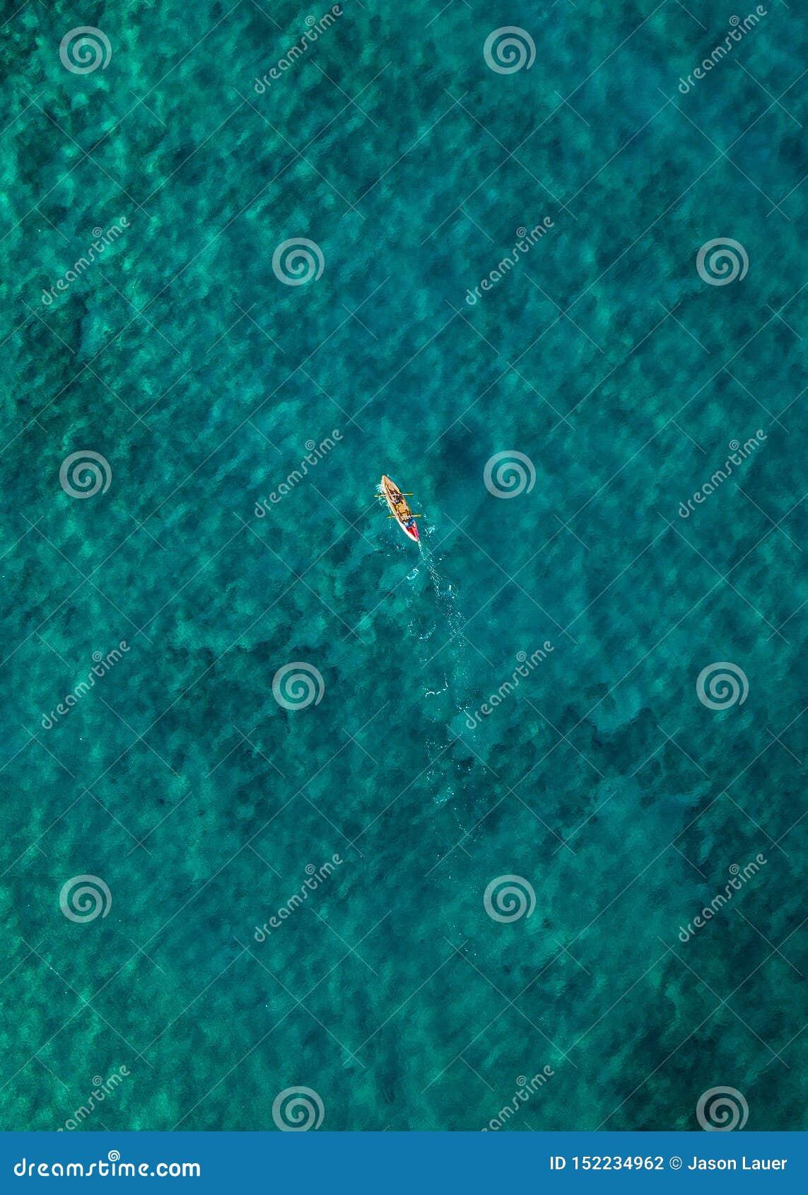 Uma pessoa solitária que kayaking na claro água da cerceta