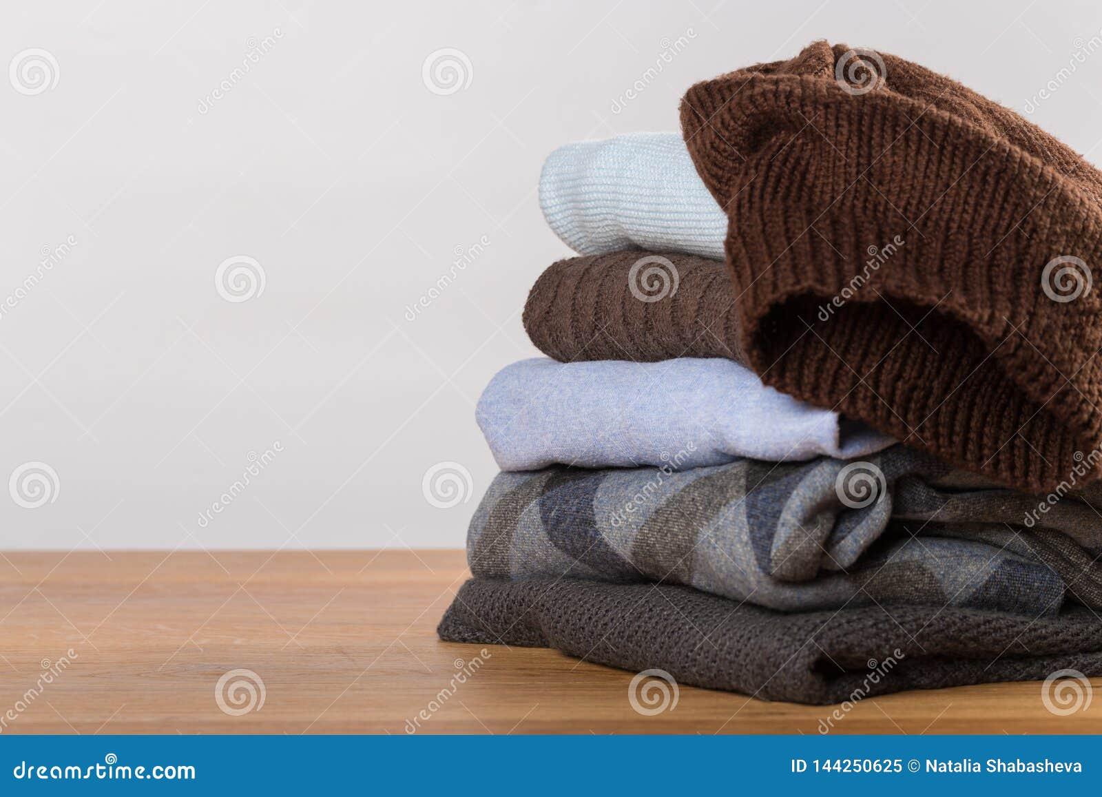 Uma pilha de camisetas mornas em uma tabela de madeira em um fundo claro Roupa do inverno