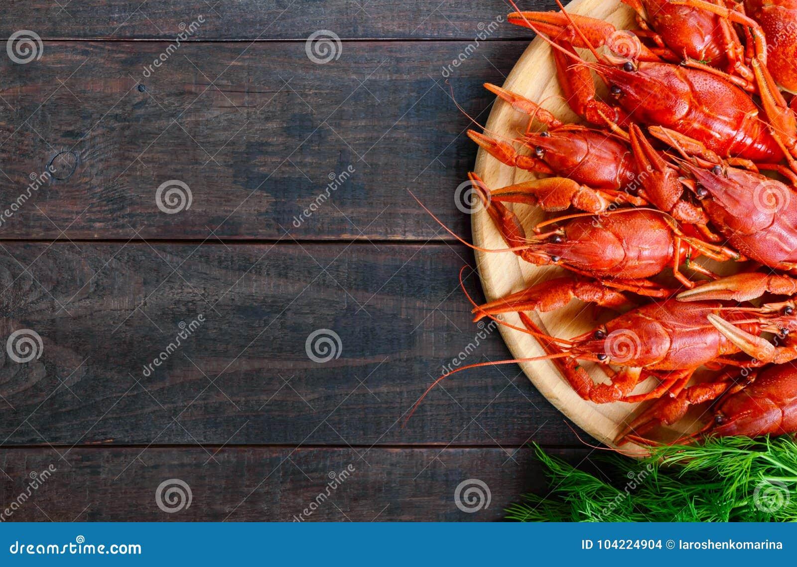 Uma pilha de lagostins fervidos saborosos em uma bandeja de madeira redonda em uma tabela escura Vista superior