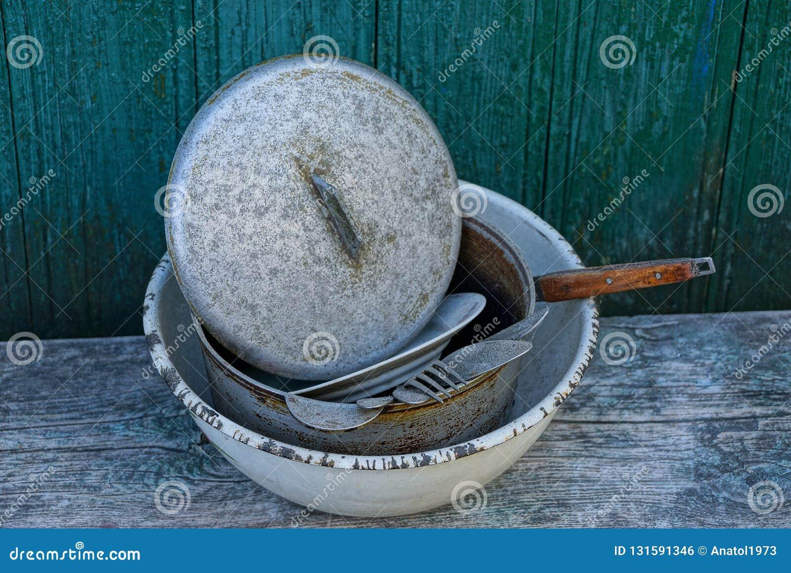 Uma pilha de pratos sujos em uma bacia cinzenta do metal em uma tabela contra uma parede verde