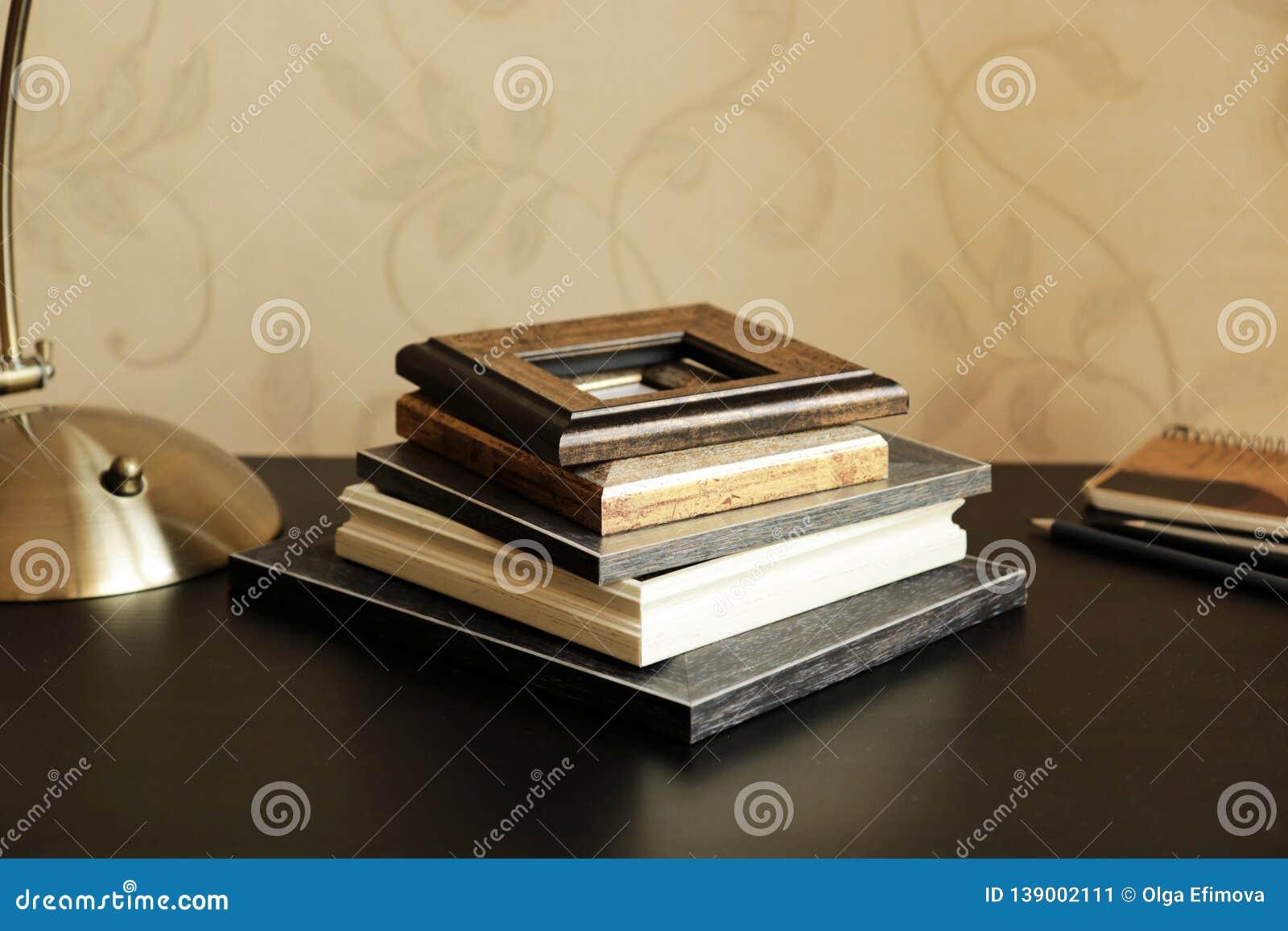 Uma pilha de quadro de madeira, de uma lâmpada, de um caderno e de lápis na mesa