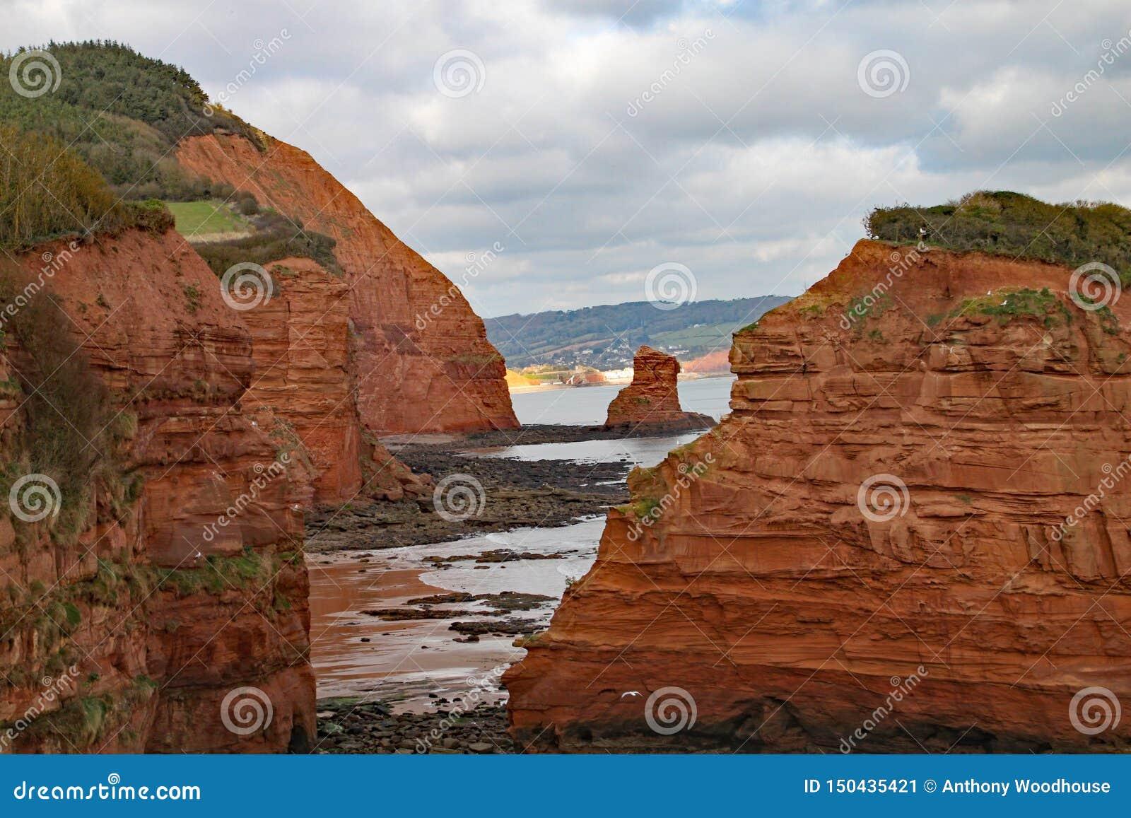 Uma pilha do mar do arenito na baía perto de Sidmouth, Devon de Ladram Peça do trajeto litoral ocidental sul Sidmouth é visível n