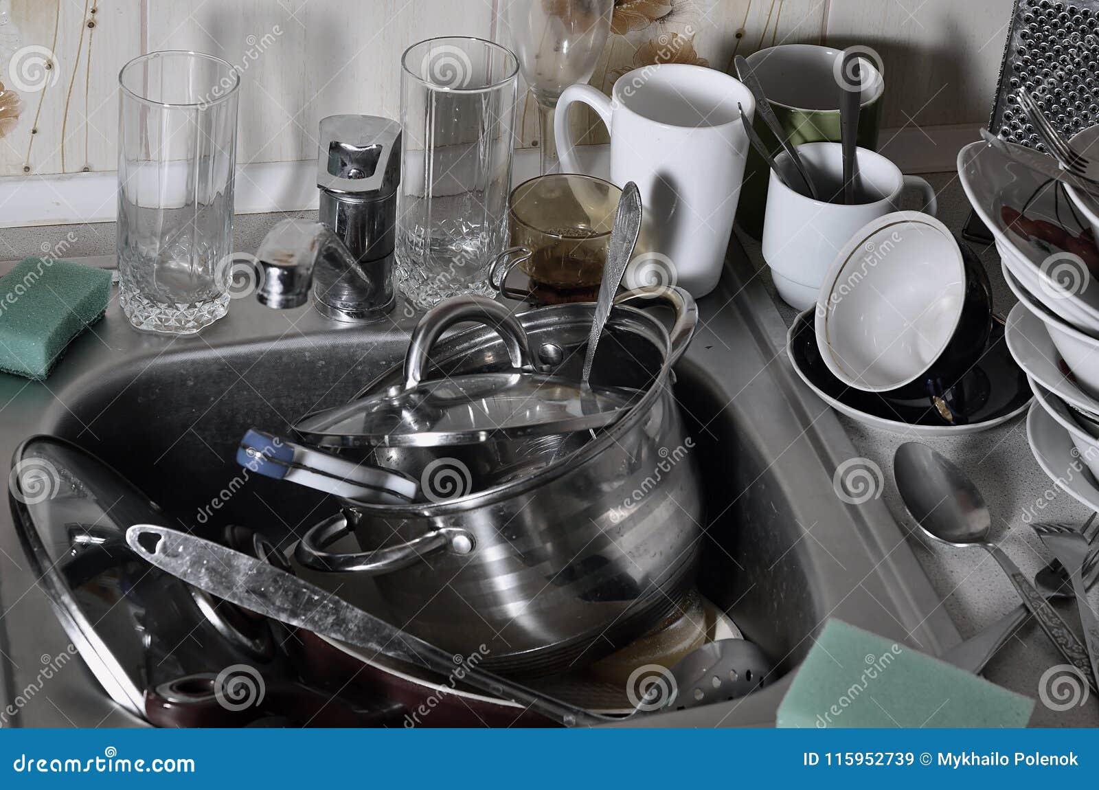 Uma pilha enorme de pratos unwashed na banca da cozinha e na bancada Muitos utensílios e dispositivos de cozinha antes de lavar