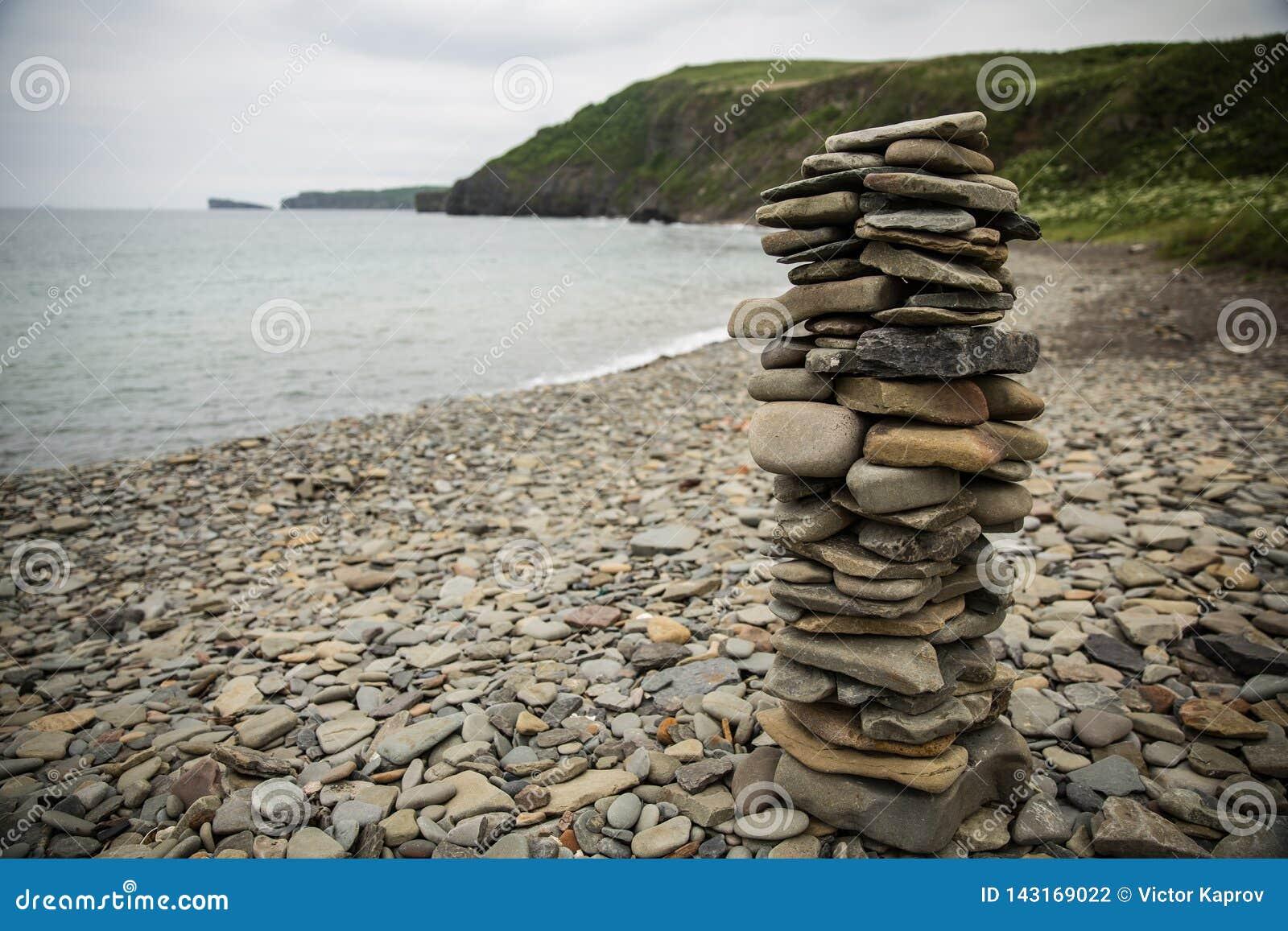 Uma pirâmide das pedras na costa do mar de japão