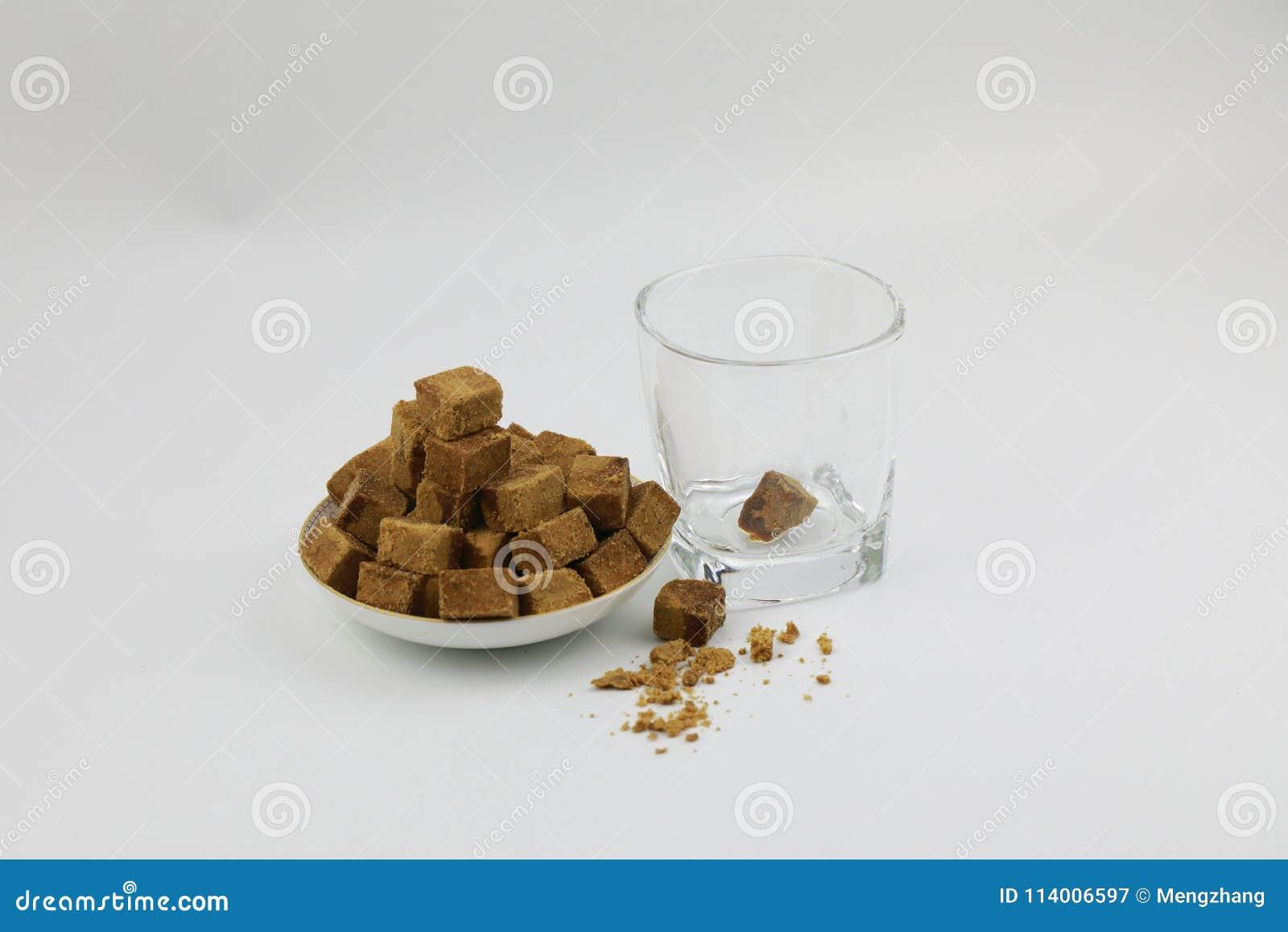 Uma placa do açúcar mascavado cuba o açúcar da rocha, vidro transparente de A ao lado, uma parte de açúcar mascavado no vidro no