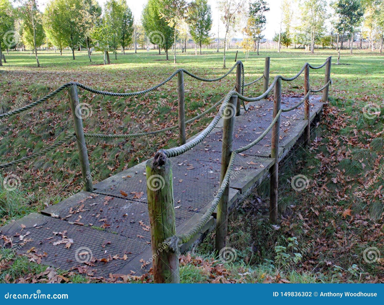 Uma ponte de corda pequena cruza uma vala no arboreto de Arley na região central da Inglaterra em Inglaterra