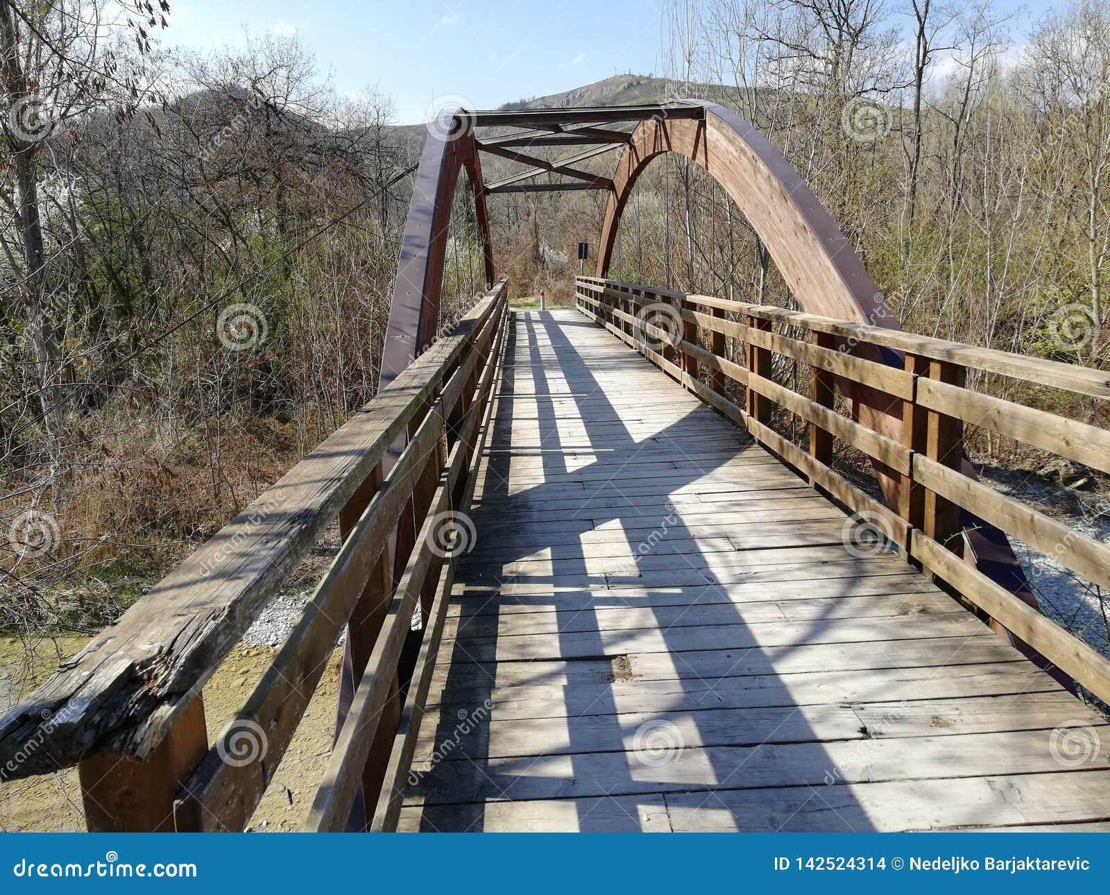 Uma ponte de madeira com um cofre-forte de madeira semicircular