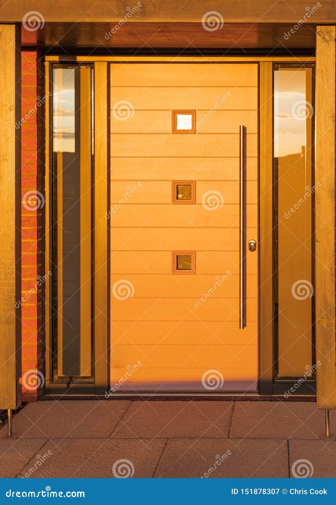 Uma porta da rua moderna nova do apartamento tomada durante um por do sol muito baixo, brilhante e amarelo