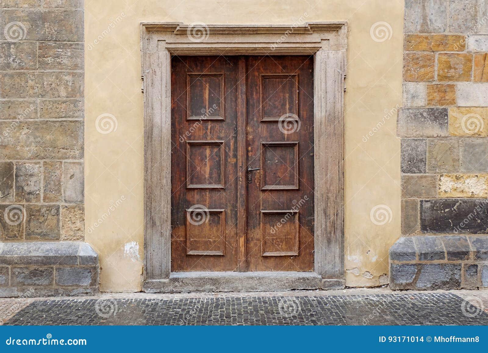 Uma porta dobro de madeira com quadro de porta do retângulo em uma parede de pedra