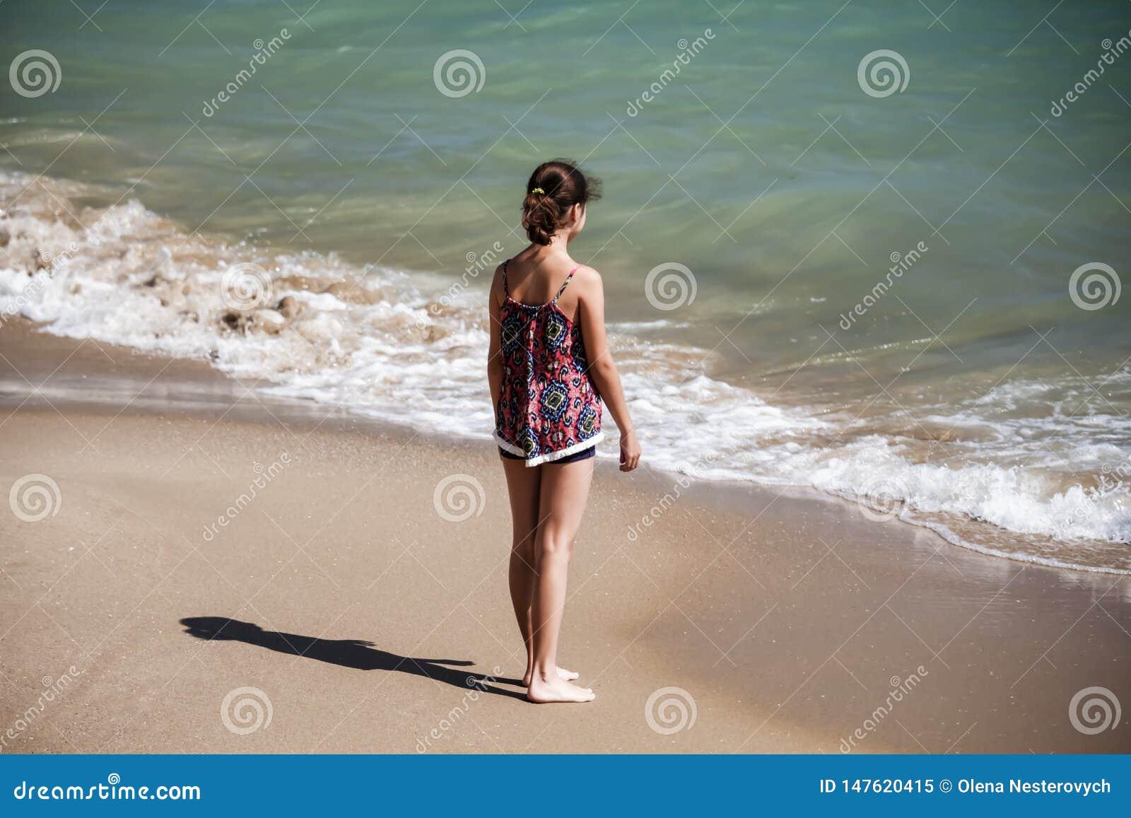 Uma posição bonita da menina na praia e vista distante no mar, fockus macio