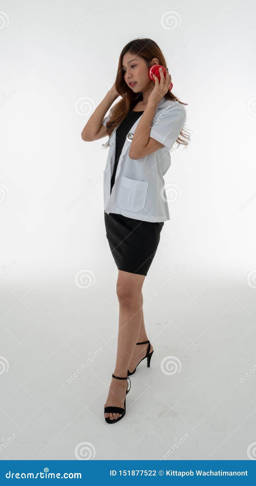 Uma posição do doutor da mulher levanta vestir uns auriculares vermelhos com um sthethoscope em seu pescoço