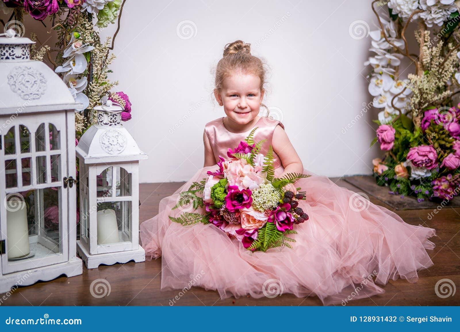 Uma princesa pequena em um vestido cor-de-rosa bonito senta-se no assoalho perto dos suportes de flor e as lanternas, guardam um