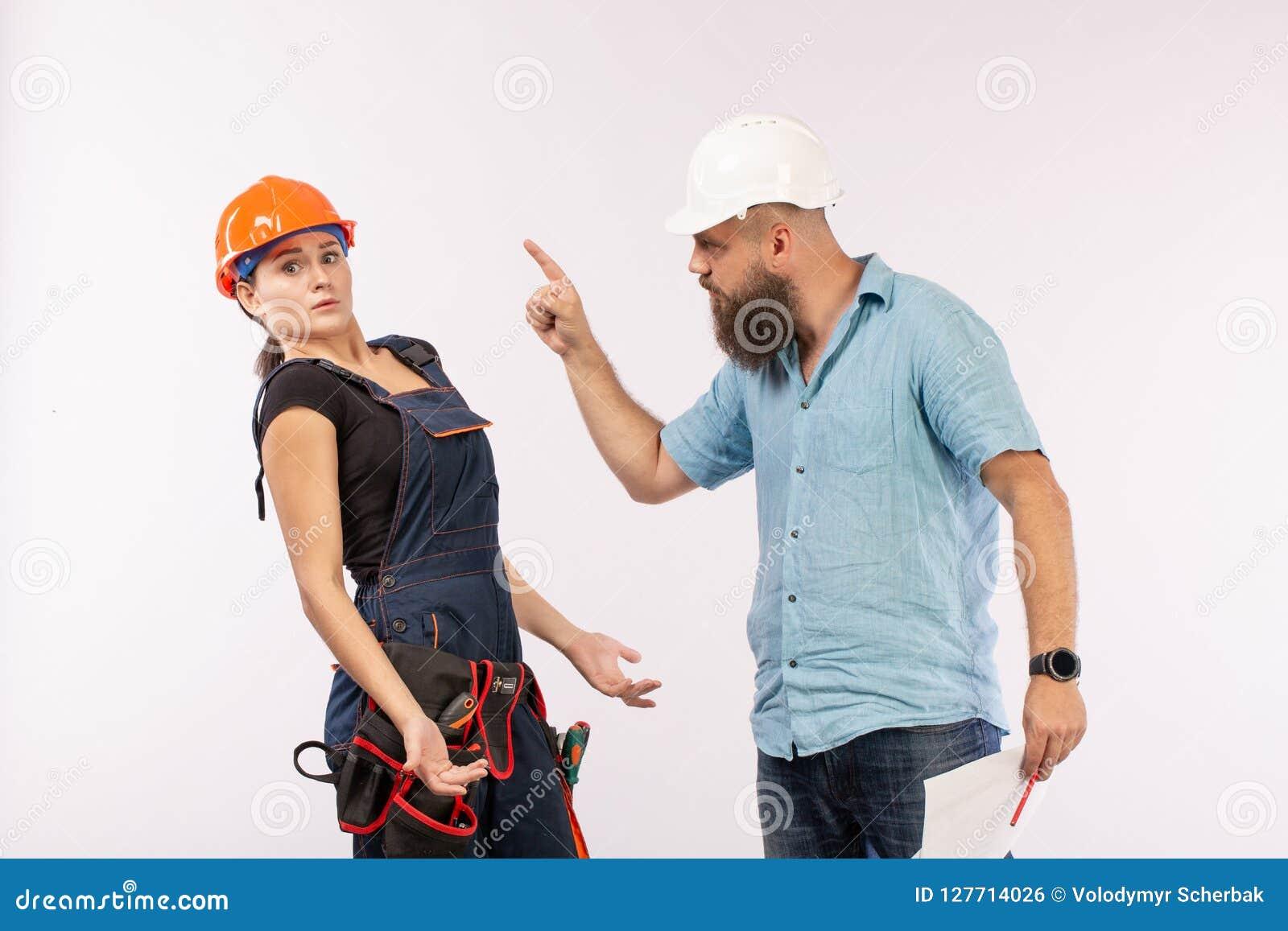 Uma reunião masculina do arquiteto ou do coordenador com um contratante da mulher da construção no fundo branco