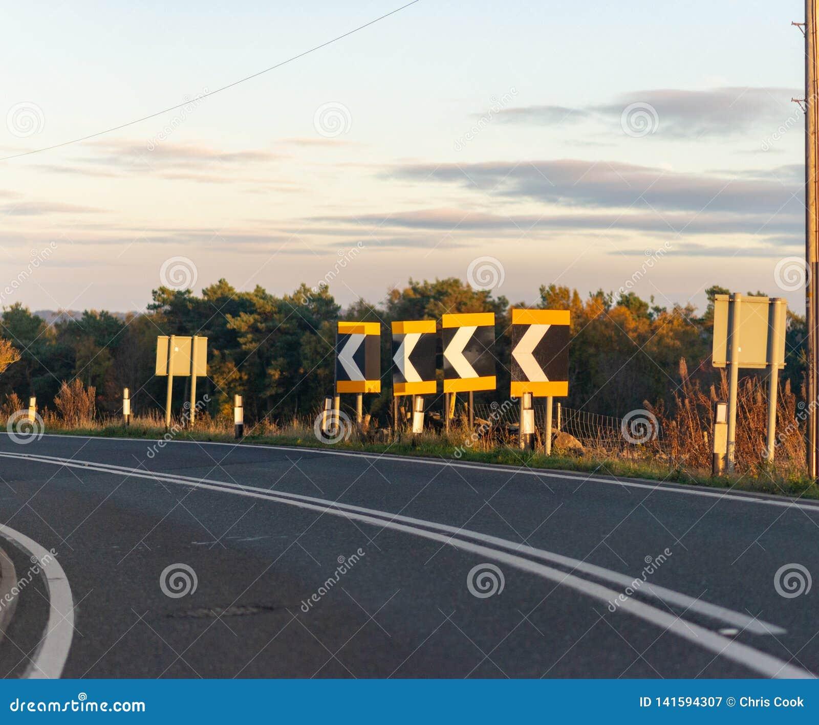 Uma série de sinais adverte motoristas de uma curvatura afiada no Reino Unido