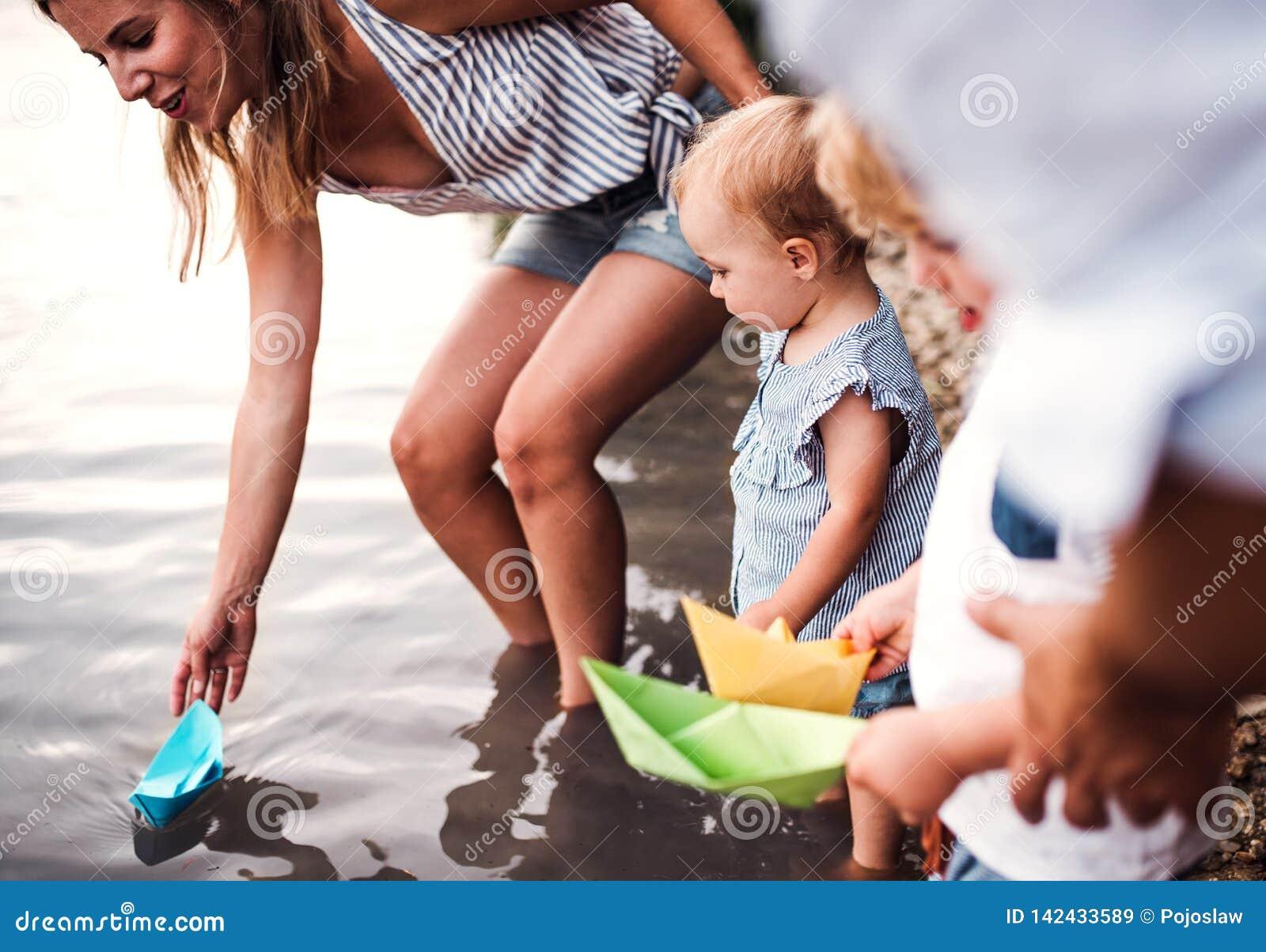 Uma seção mestra da família com as duas crianças da criança fora pelo rio no verão