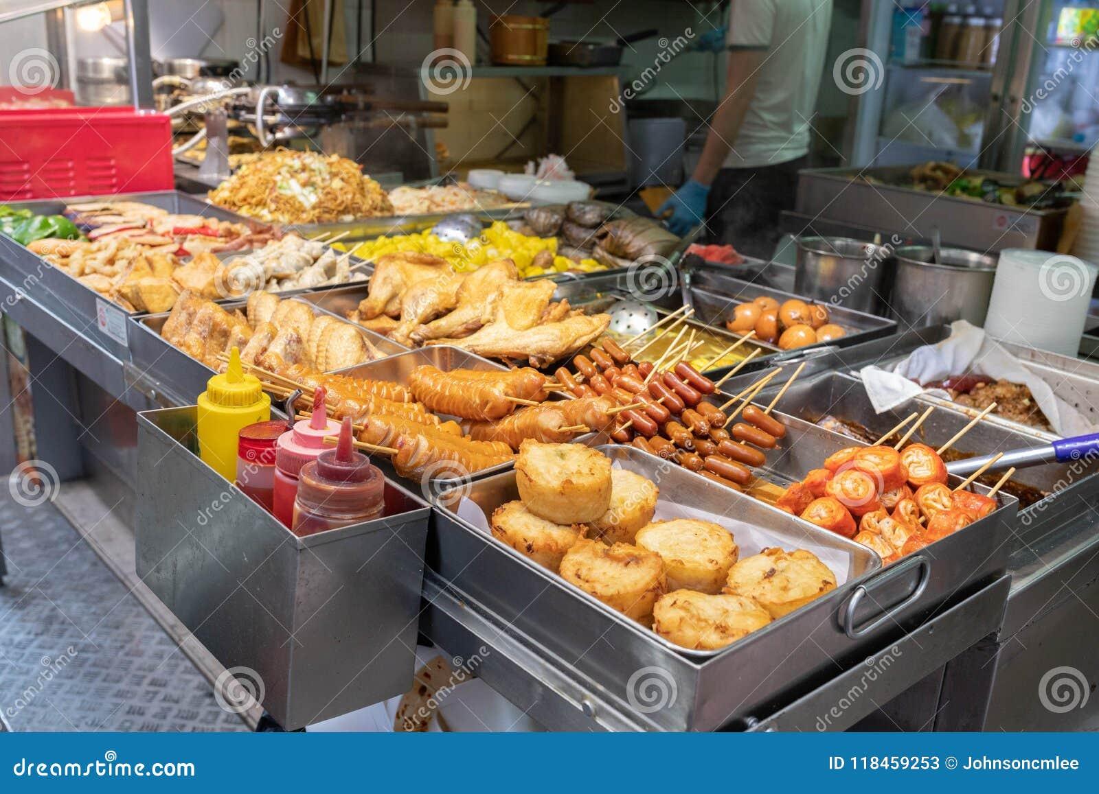 Uma tenda do alimento da rua em Hong Kong que vende tipos diferentes de frita e assou o alimento Demonstrando a cultura asiática
