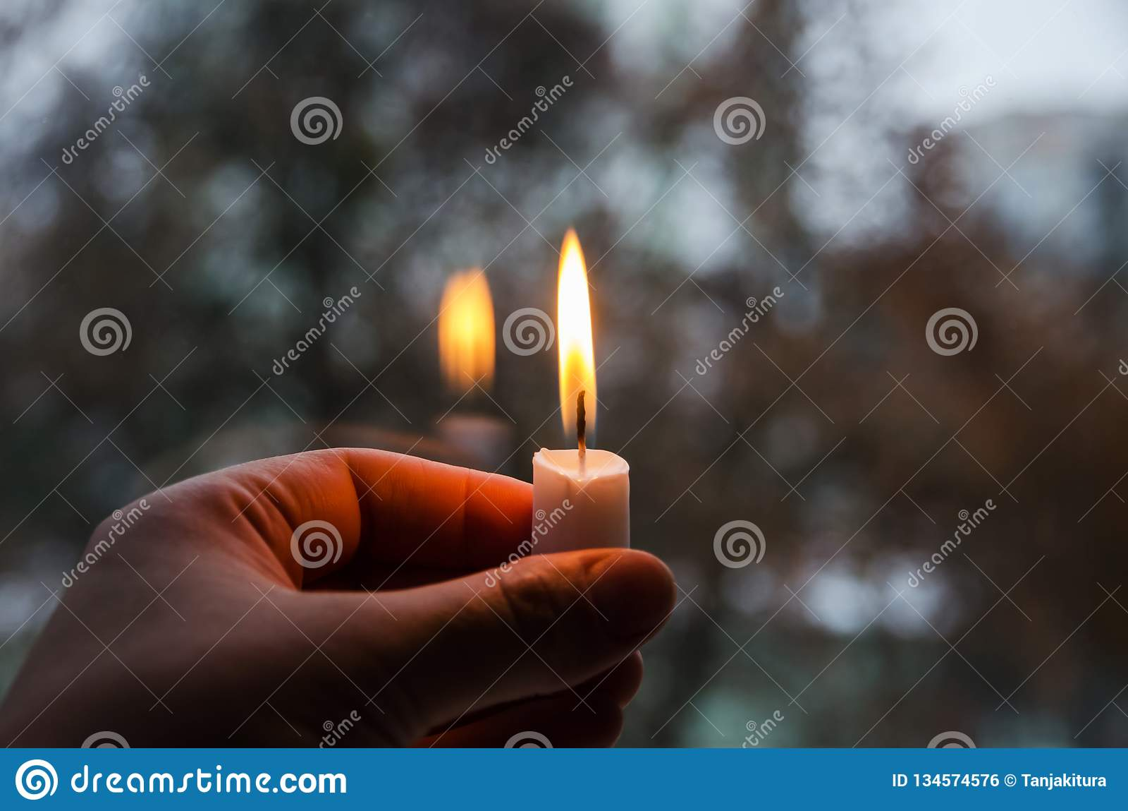 Uma vela iluminada na mão de uma mulher