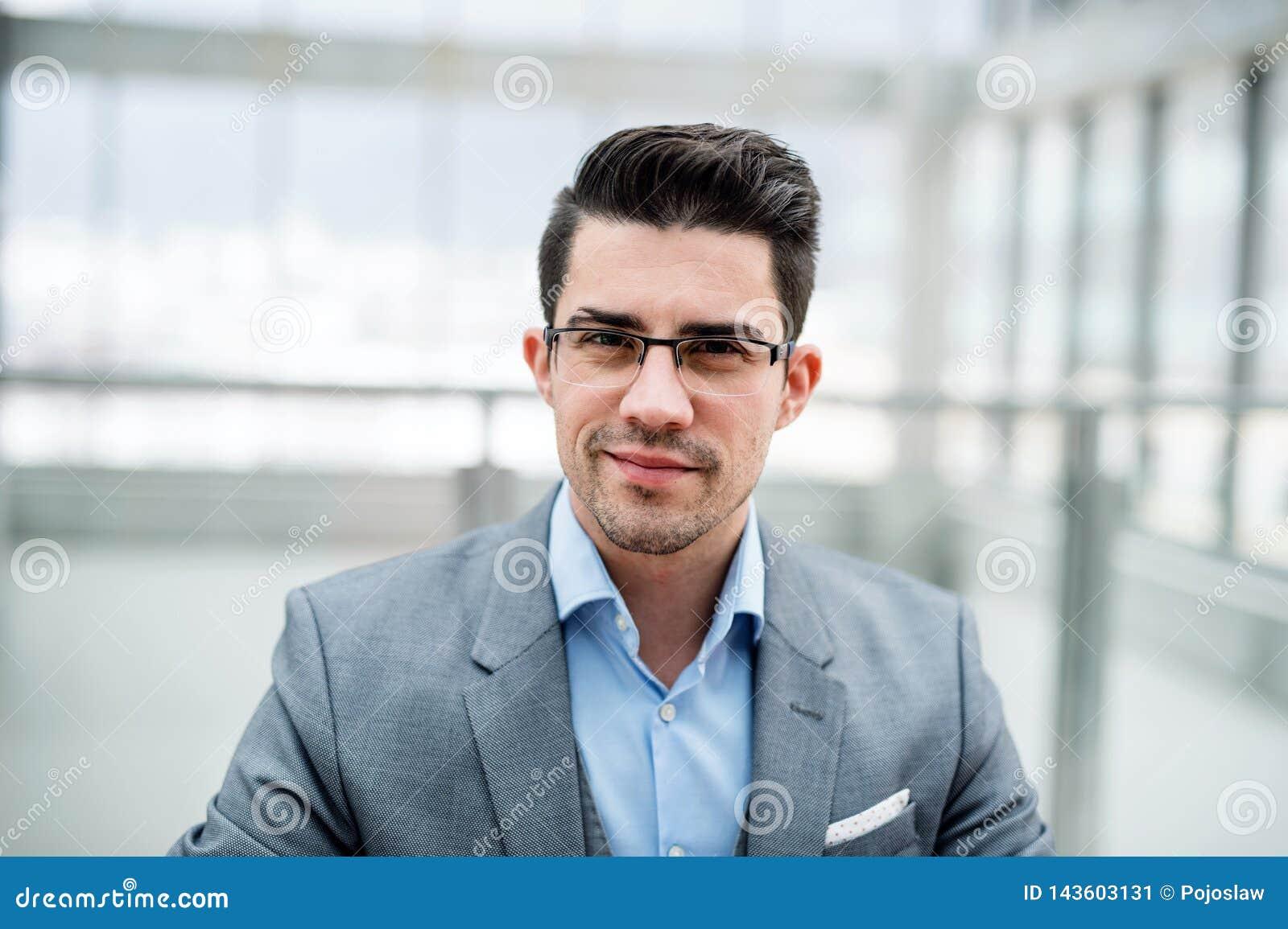 Uma vista dianteira do retrato do homem de negócios novo dentro em um escritório