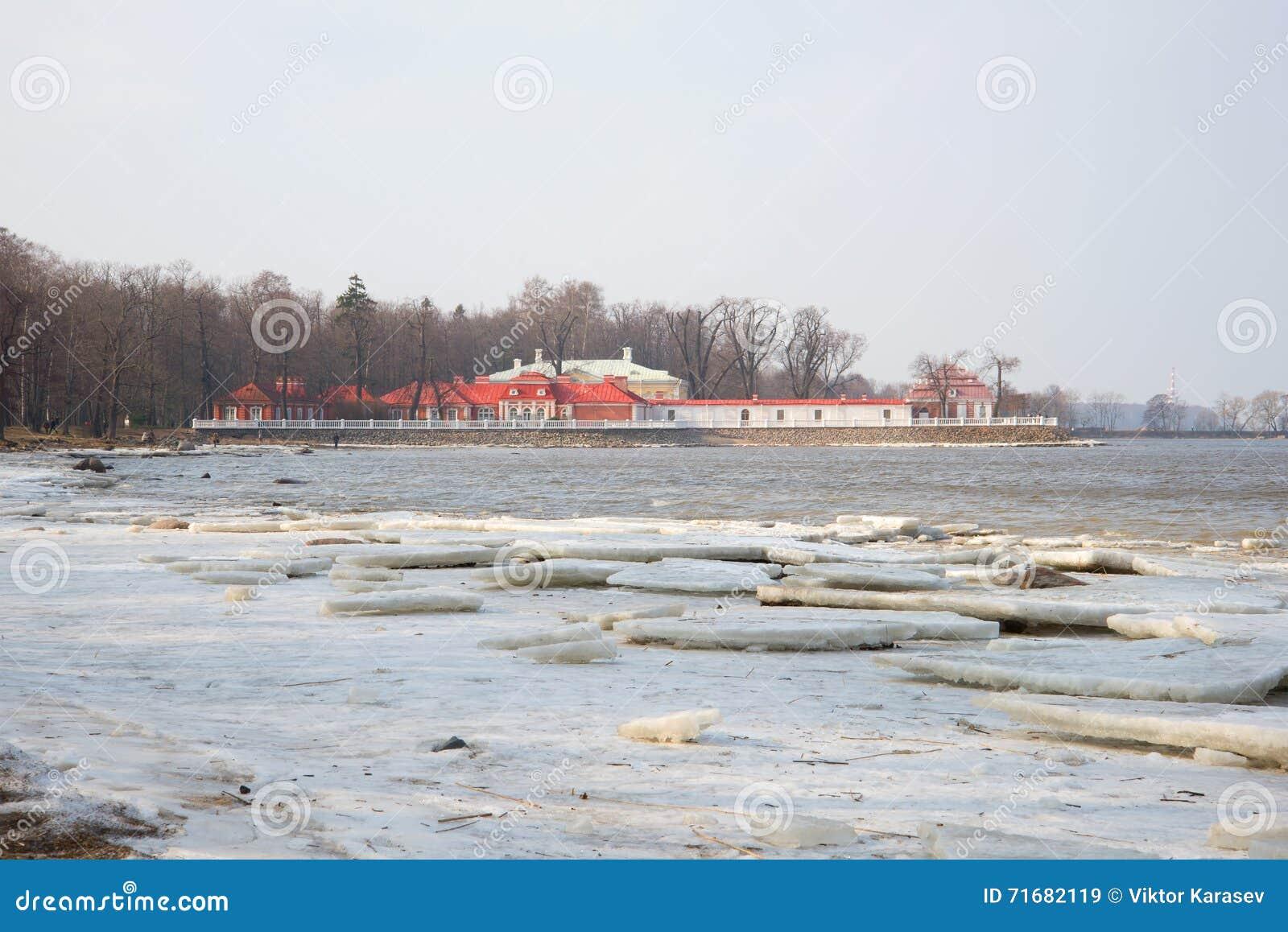 Uma vista do palácio de Monplaisir no Golfo da Finlândia, tarde do março Peterhof