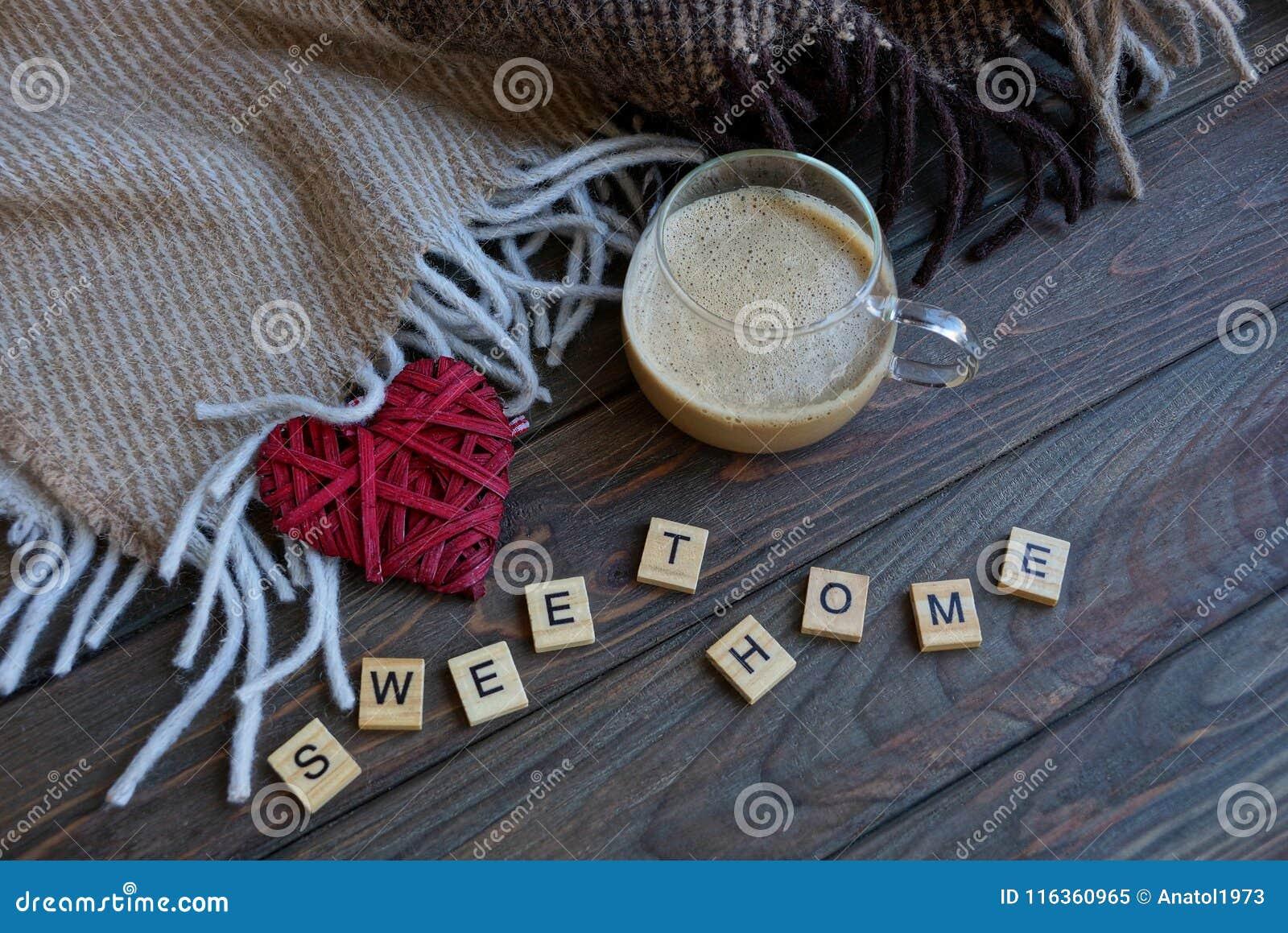Uma xícara de café e um coração vermelho perto de uma cobertura de lã na tabela com uma palavra da casa de madeira do doce das le