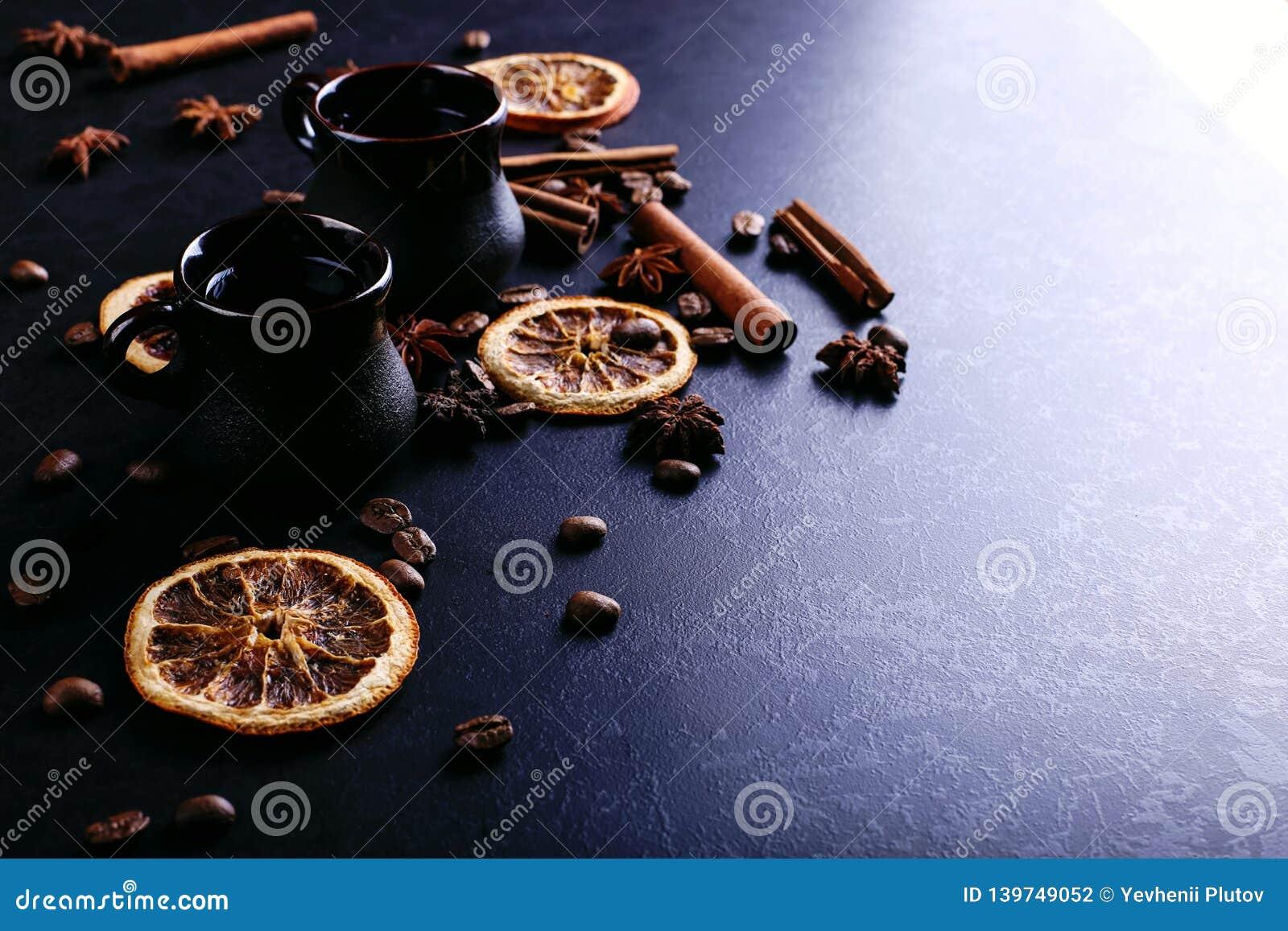 Uma xícara de café, um anis de estrela, uma canela, uma laranja secada e uns feijões de café em uma bancada escura da cozinha Esp