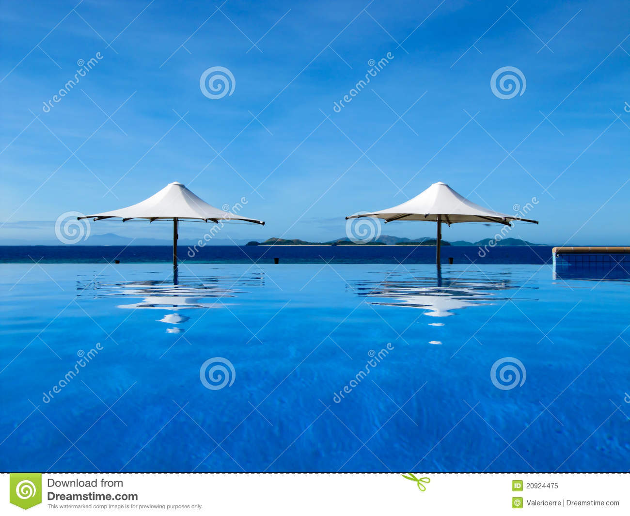 Umbrella between an infinity pool and the sea