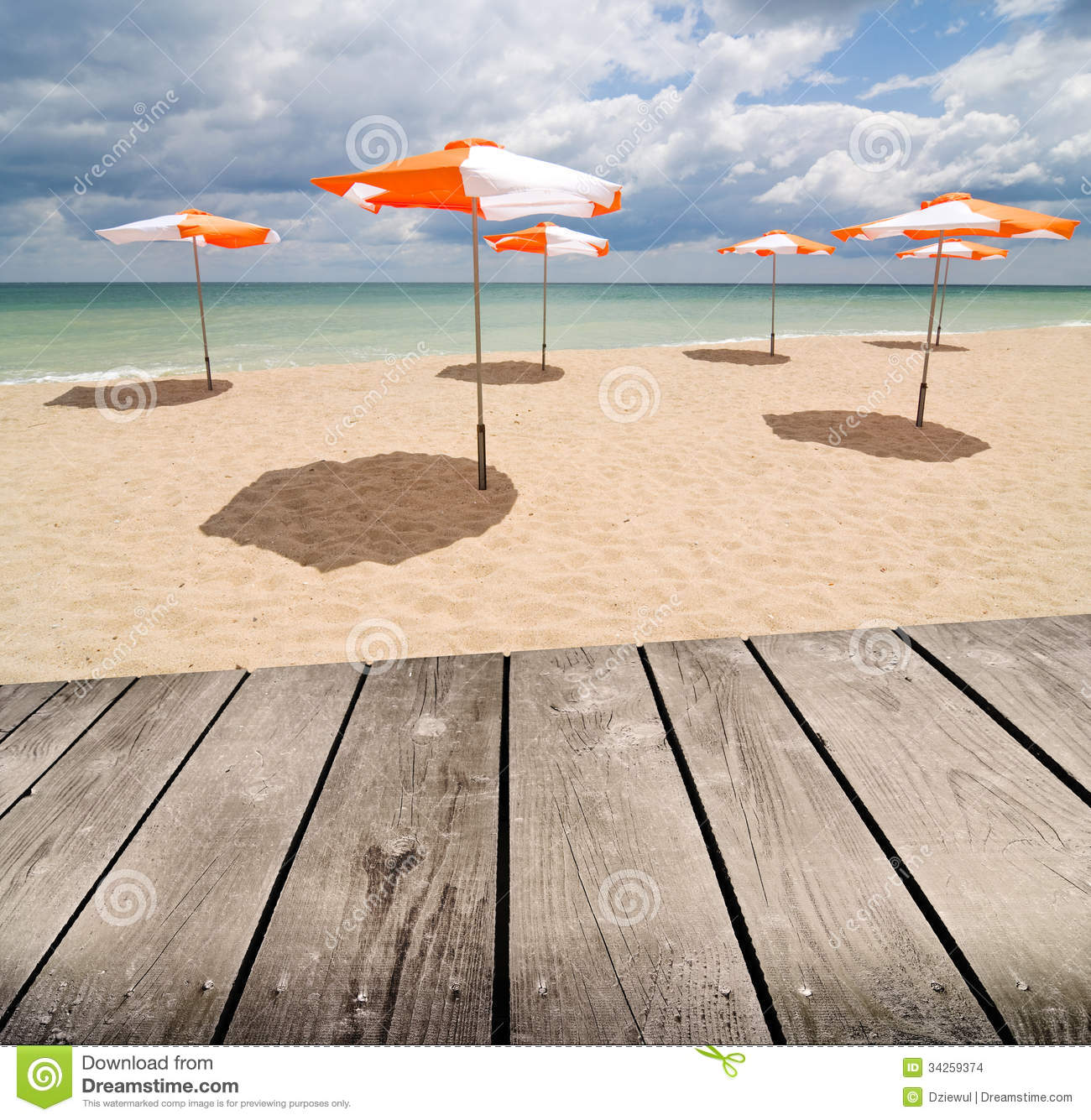 Umbrellas On The Beach And Empty Wooden Deck Table Stock