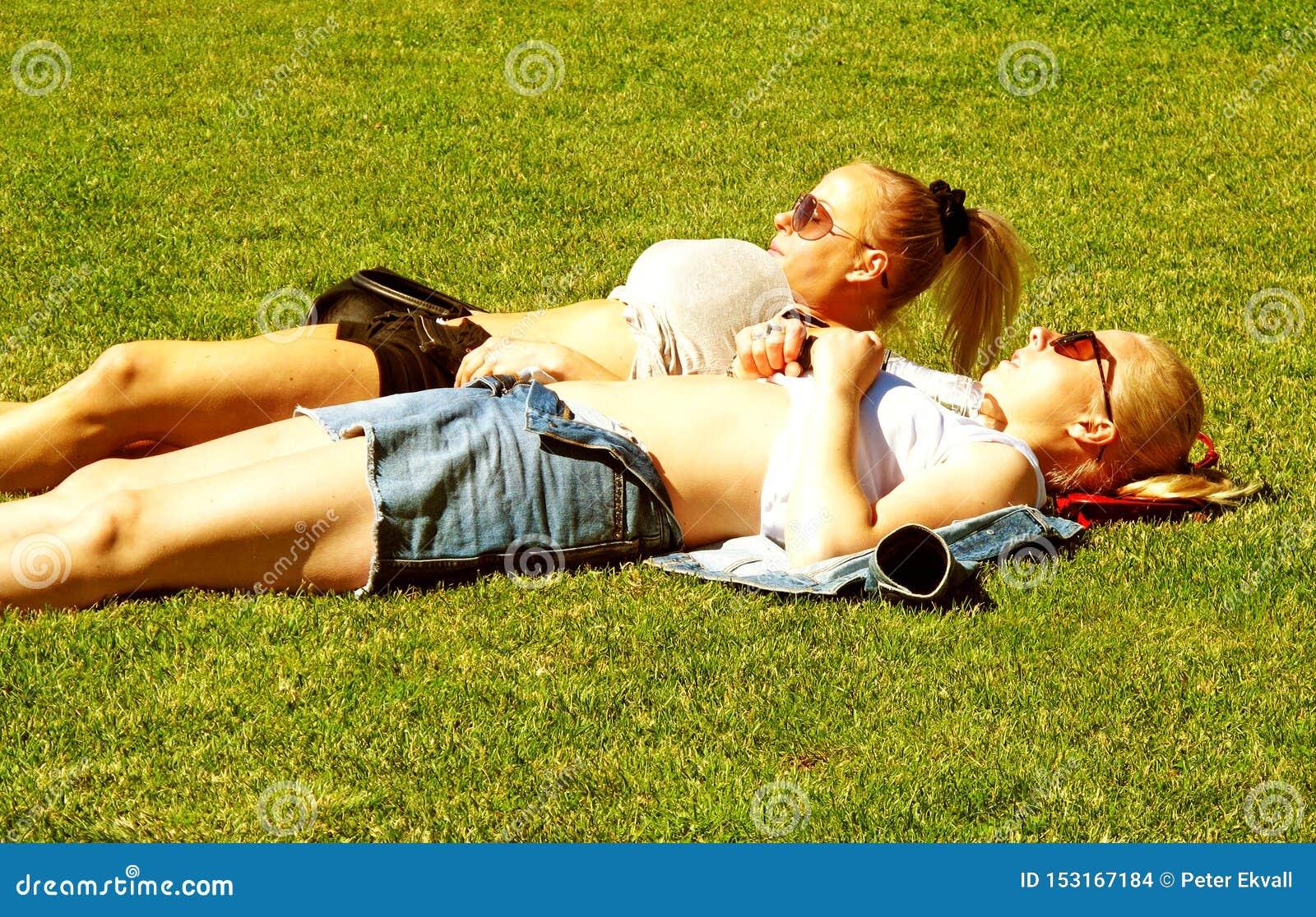 Two girls sunbathing in central park